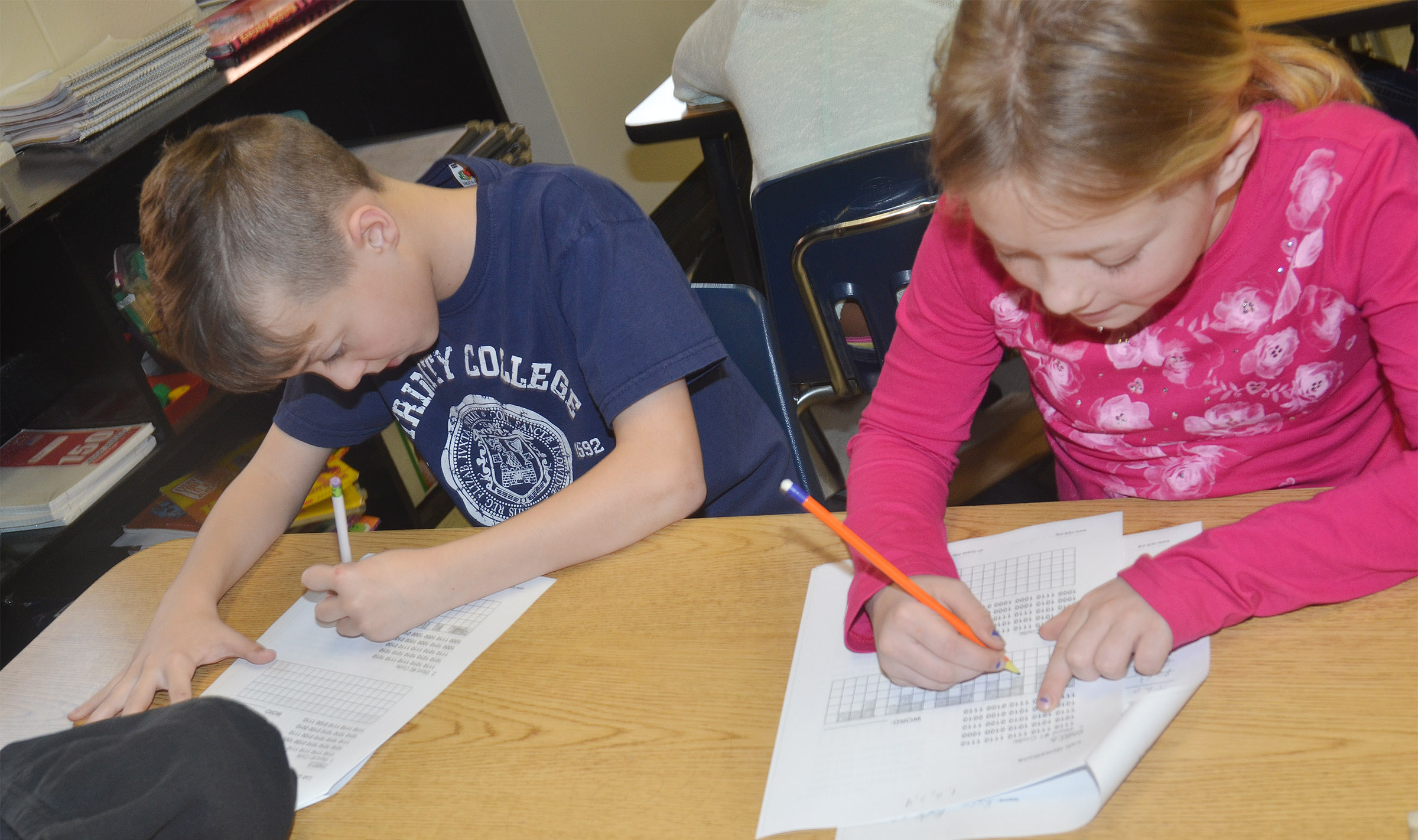 CMS fourth-graders Noah Skaggs, at left, and Kyra Parker decipher binary codes.