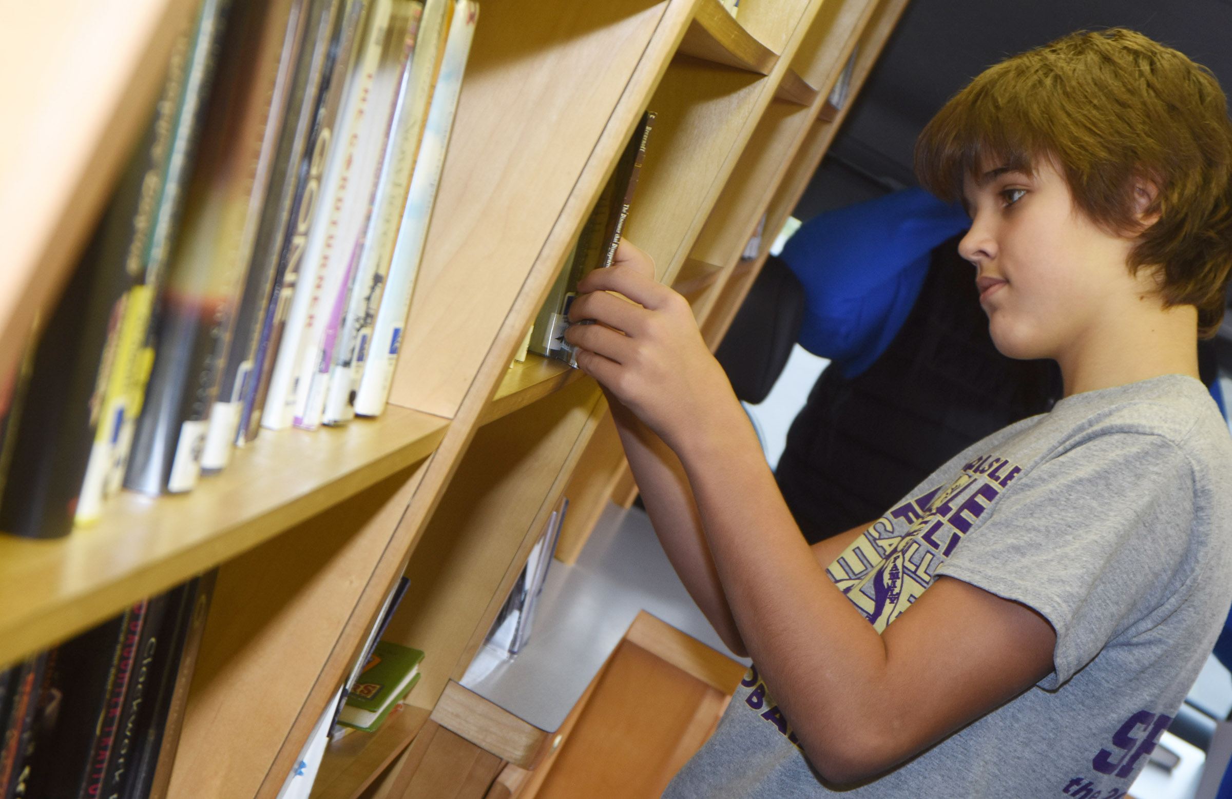 CMS seventh-grader Kaden Bloyd looks for a book on the bookmobile.