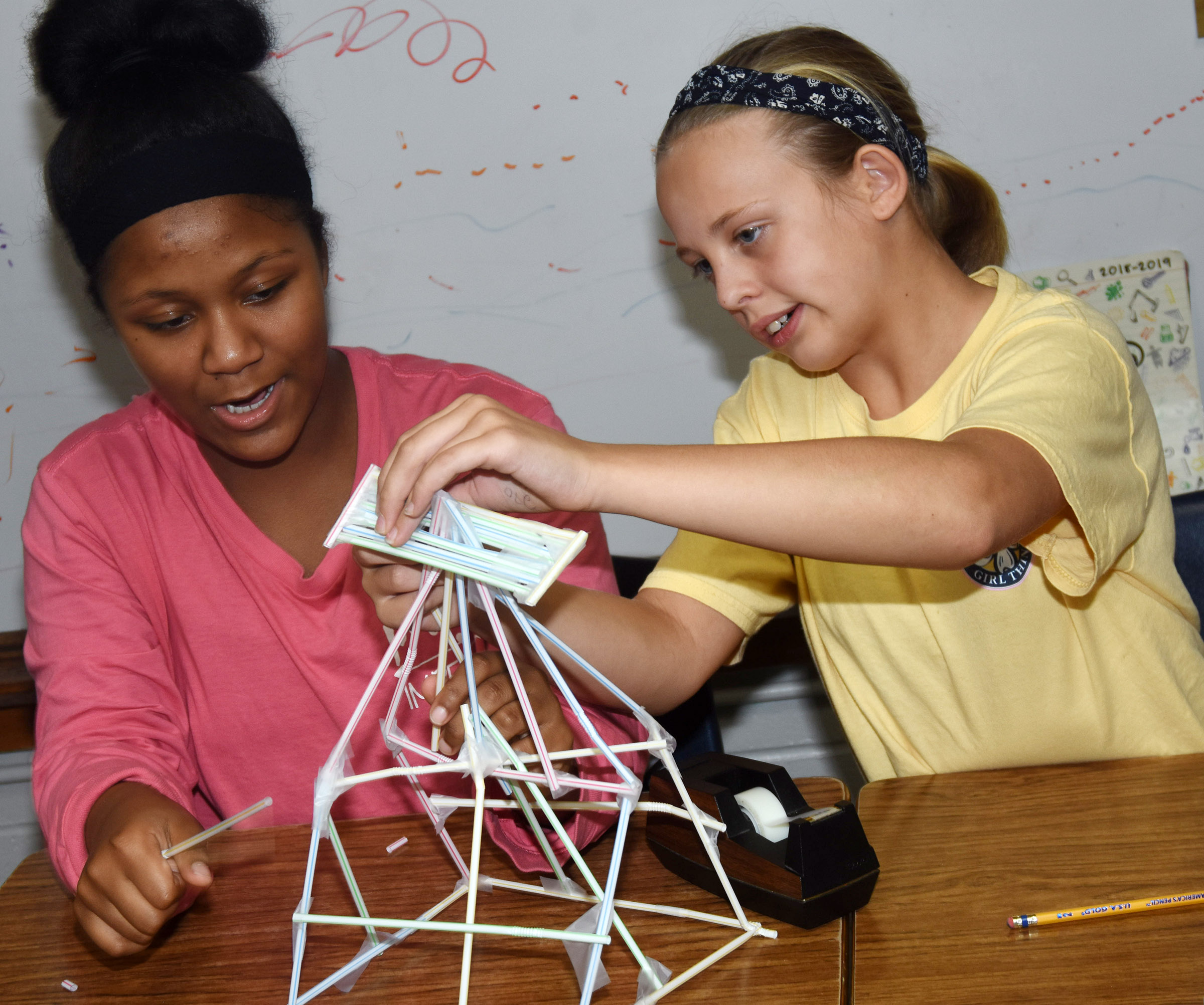 CMS seventh-graders Camilla Taylor, at left, and Gabby Bright build their structures.