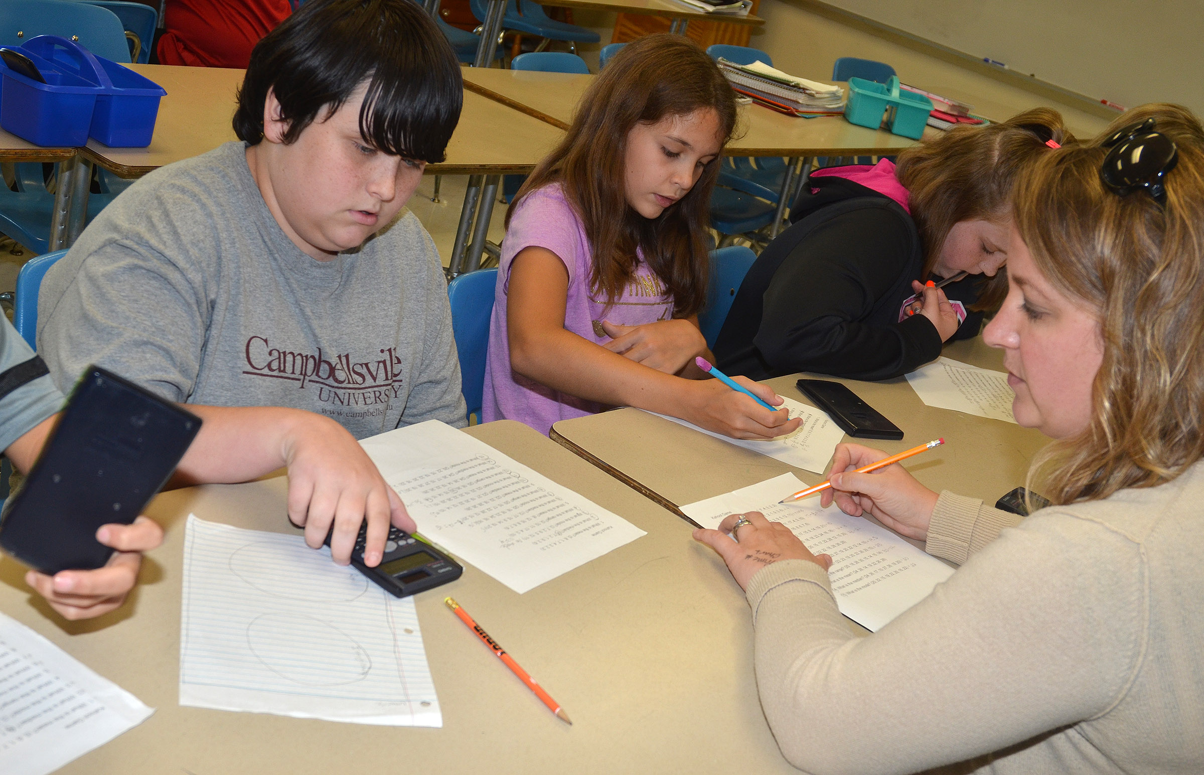 CMS teacher Katie Campbell helps sixth-graders, from left, Miles Wright, Makayla Dudley and Piper Ritchie find the median of a set of numbers.