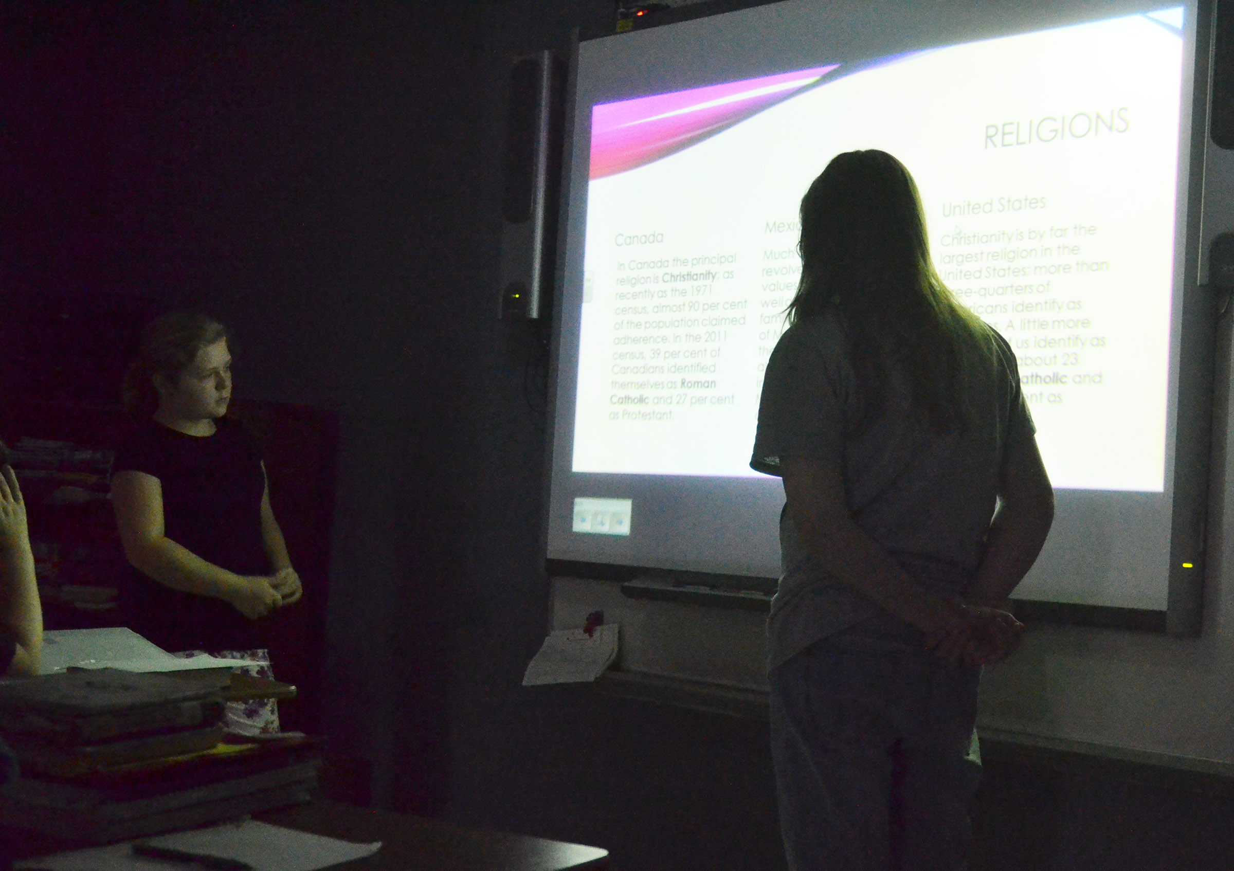 CMS sixth-graders Alexis Sharp, at left, and Savannah Riley talk about religions in Canada, Mexico and the United States.