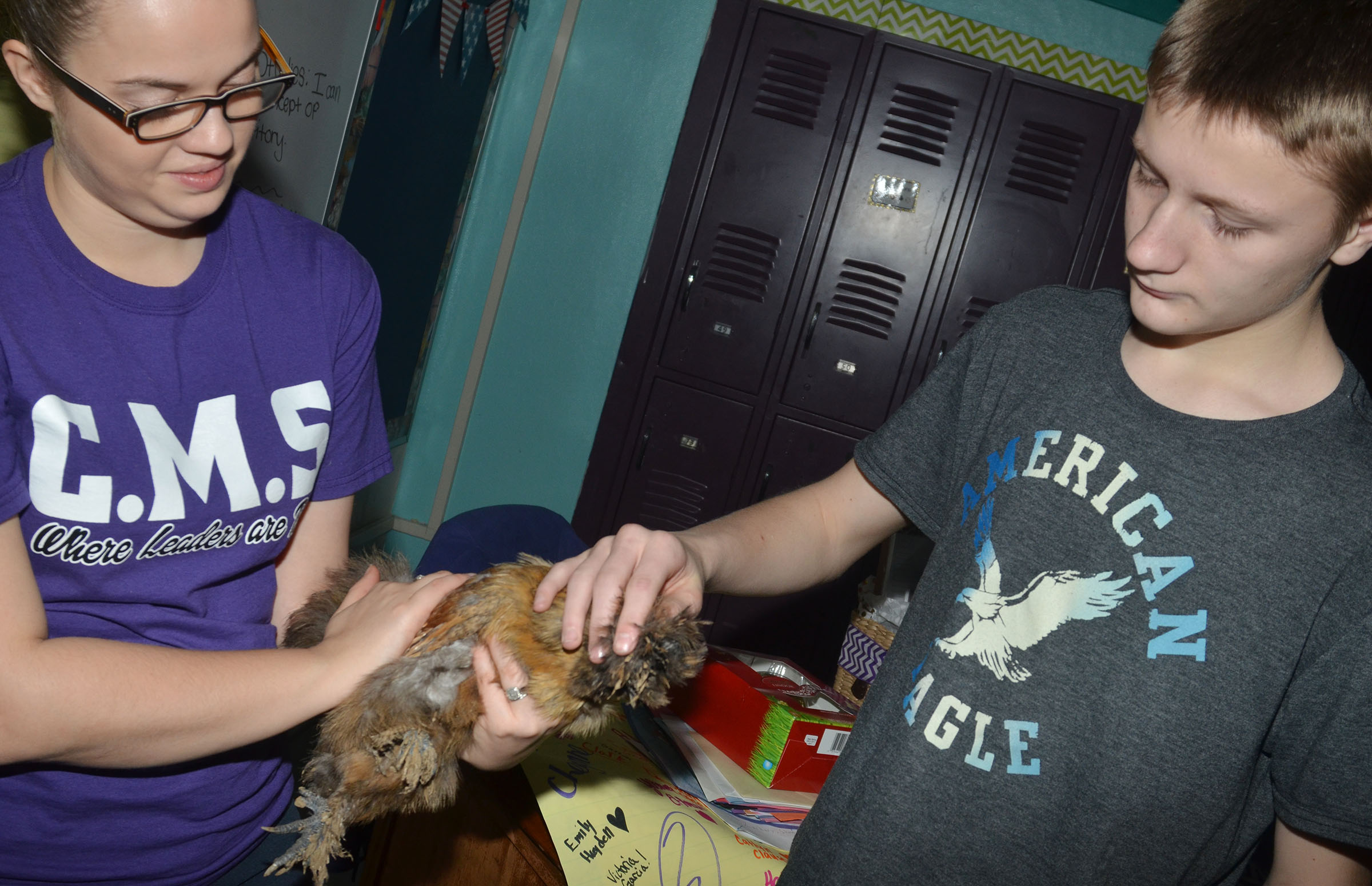 CMS student teacher Jessica Hogue holds a silkie chicken as eighth-grader Jake Dicken touches it.