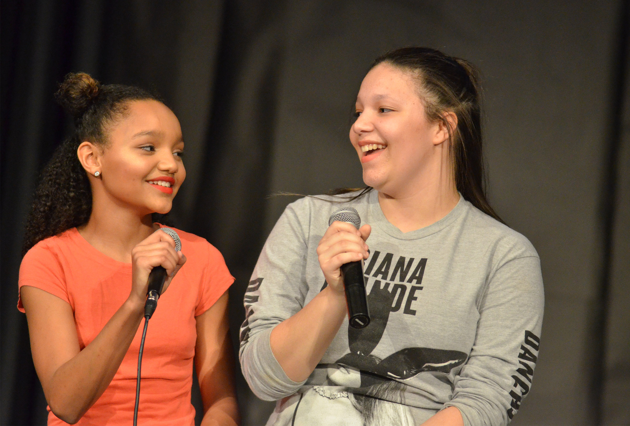 CMS seventh-grader Alexis Thomas, at left, and eighth-grader Tierra Bridgewater sing together.