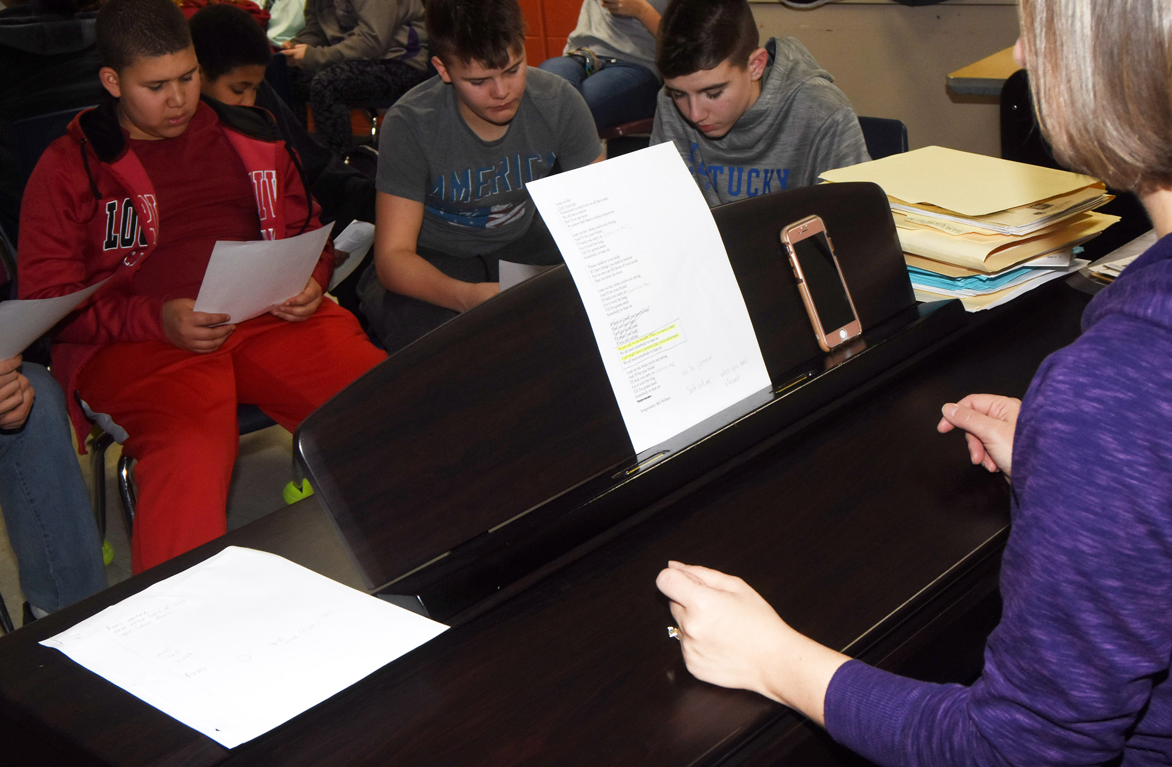 "CMS choir director Jessica Floyd leads her students as they learn the lyrics to ""Lean On Me."" From left are eighth-graders Zeke Bell, Konner Forbis and Bryce Newton."