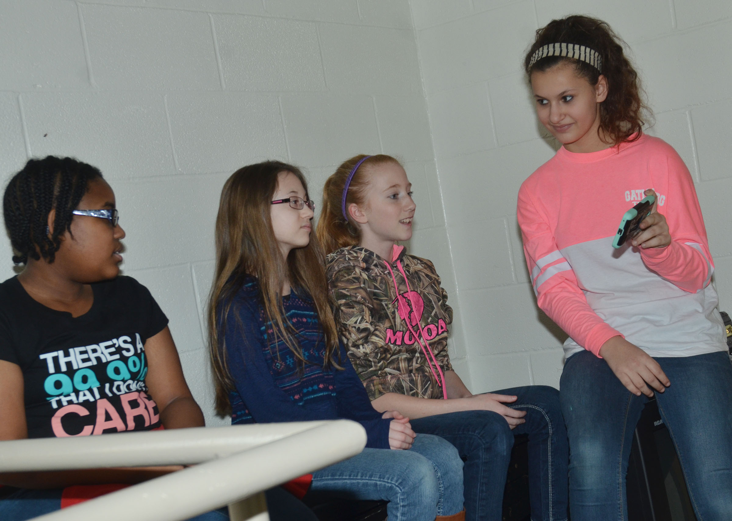 CMS eighth-grader Jasmine Mitchell, at left, and seventh-graders, from left, Cailet Clark, Hayley Wethington and Christina Miller practice the song they will sing together.