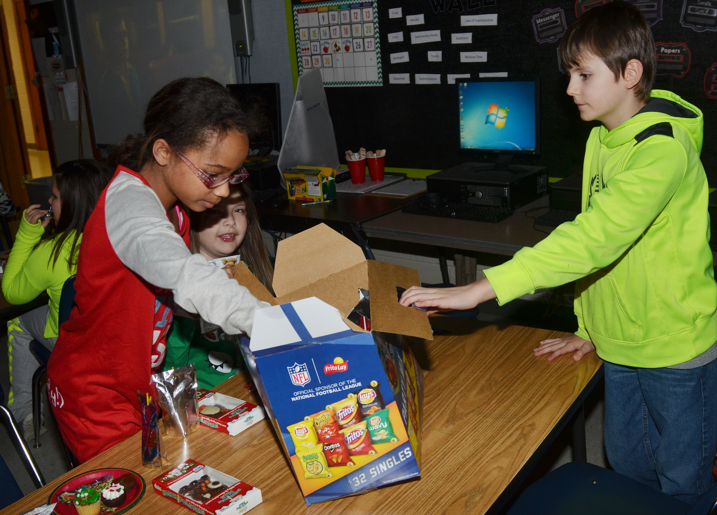 CMS fourth-grader Lillian Sears gets a bag of chips to eat during her class's Christmas party.