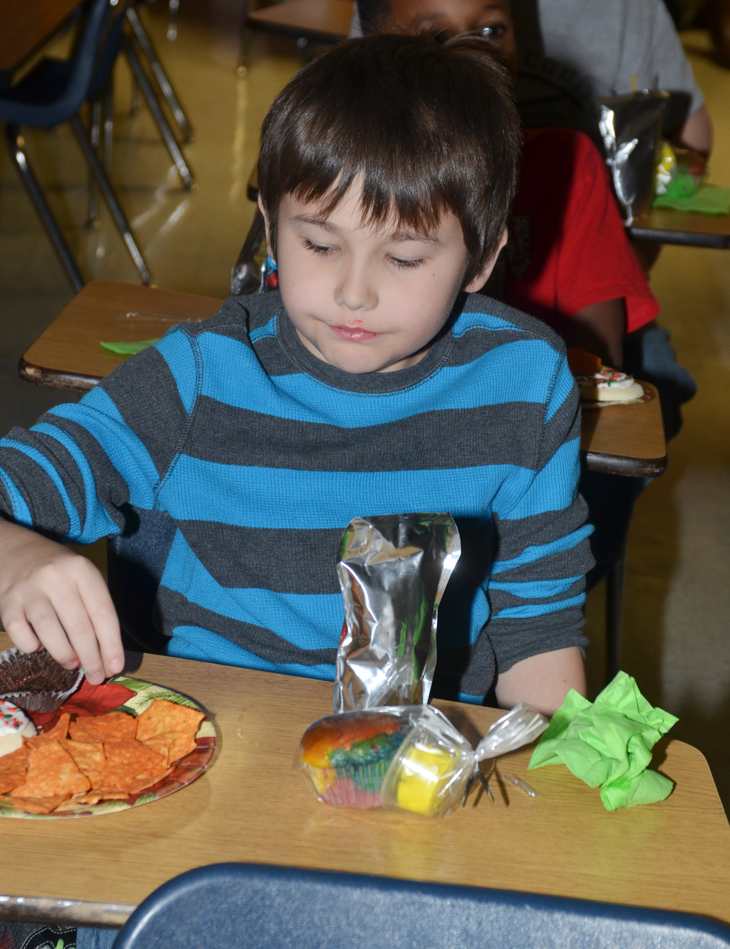 CMS fourth-grader Michael Abel enjoys snacks while watching a Christmas movie.