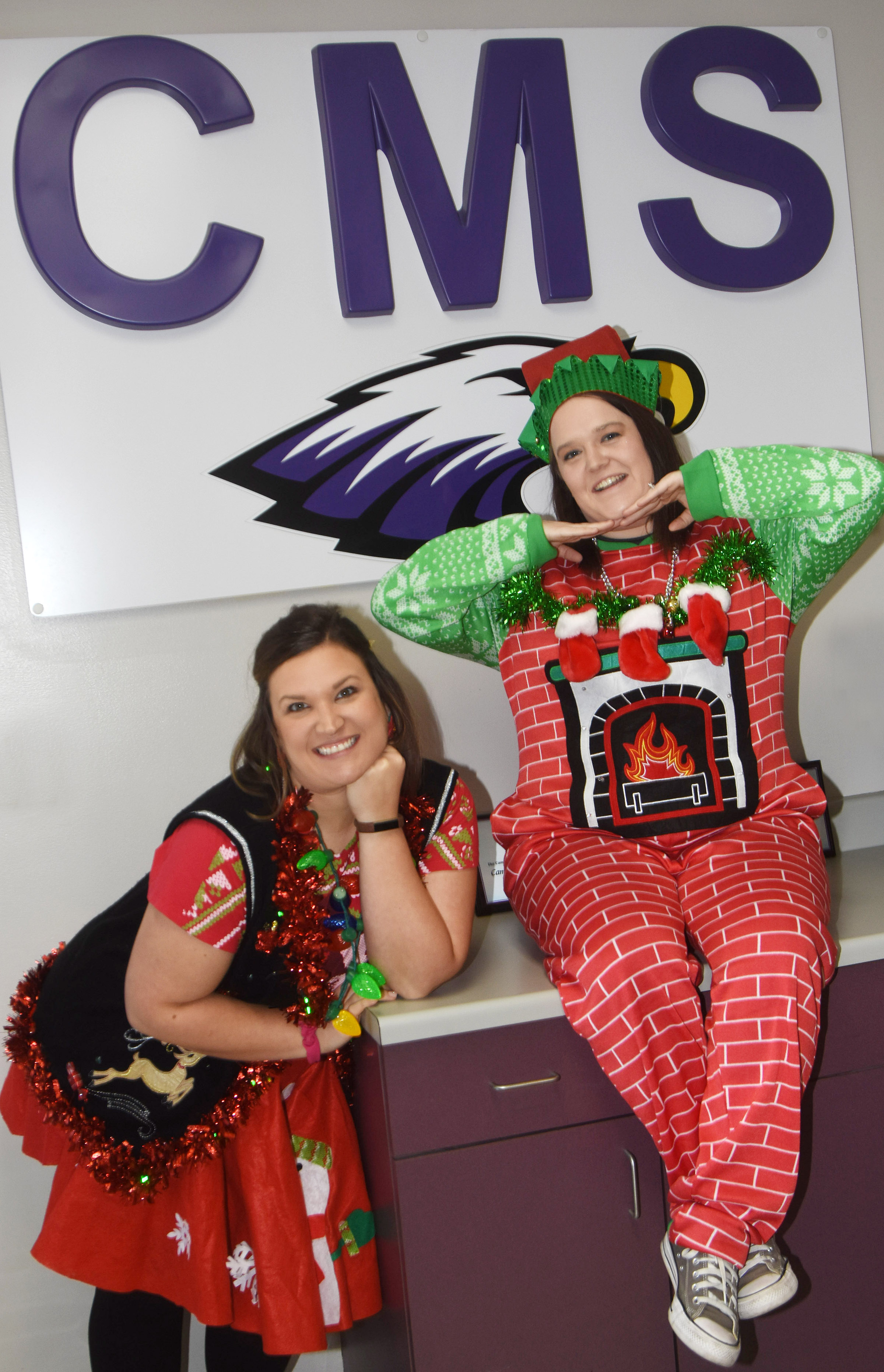 CMS eighth-grade teachers Robbilyn Speer, at left, and Paige Cook pose in their Christmas attire.