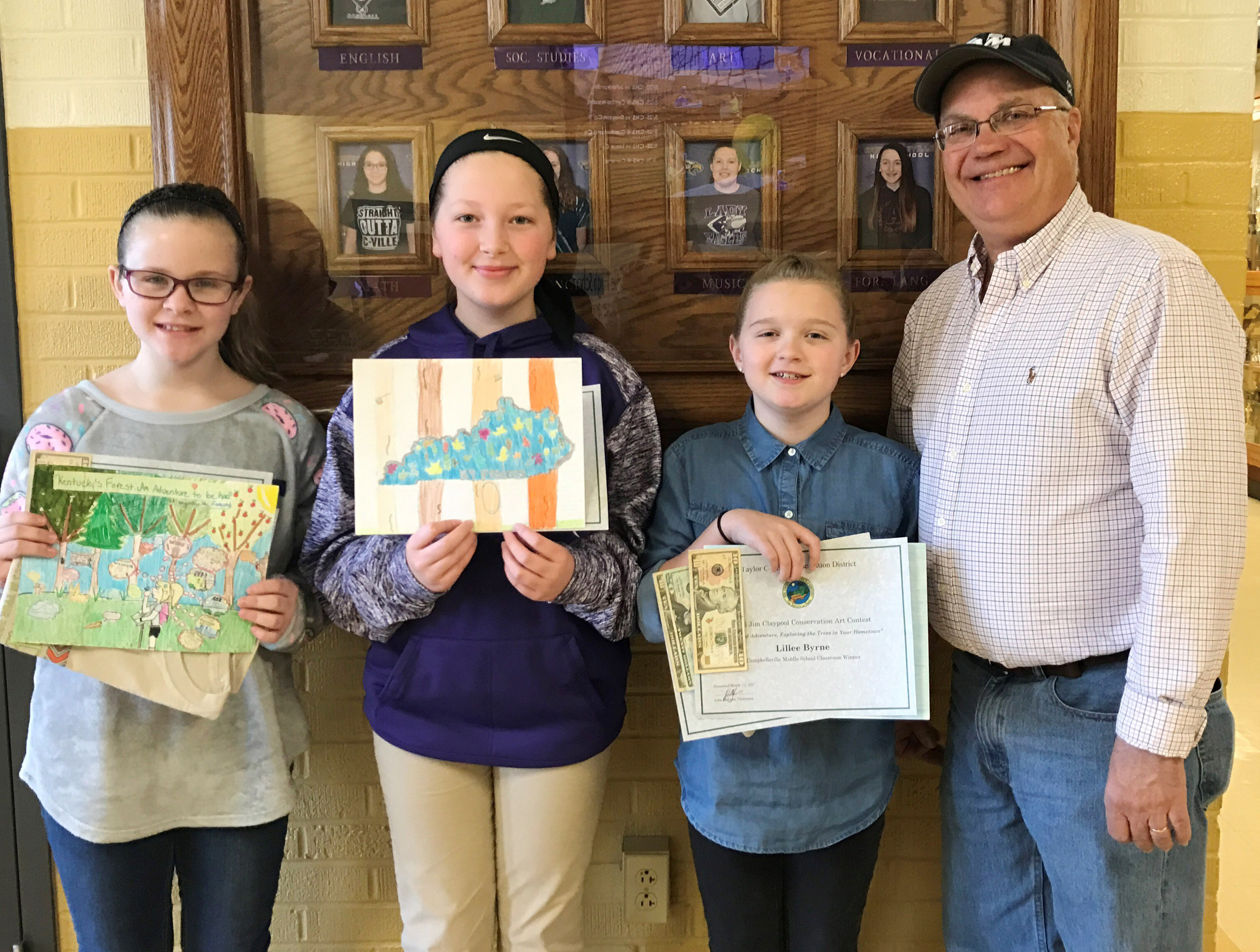 CMS art winners are, from left, fifth-graders Karlie Cox, Ava Hughes and Lillee Byrne, who are classroom winners, and Taylor County Conservation District Board Member Barry Smith. Byrne was also the overall winner for her school.