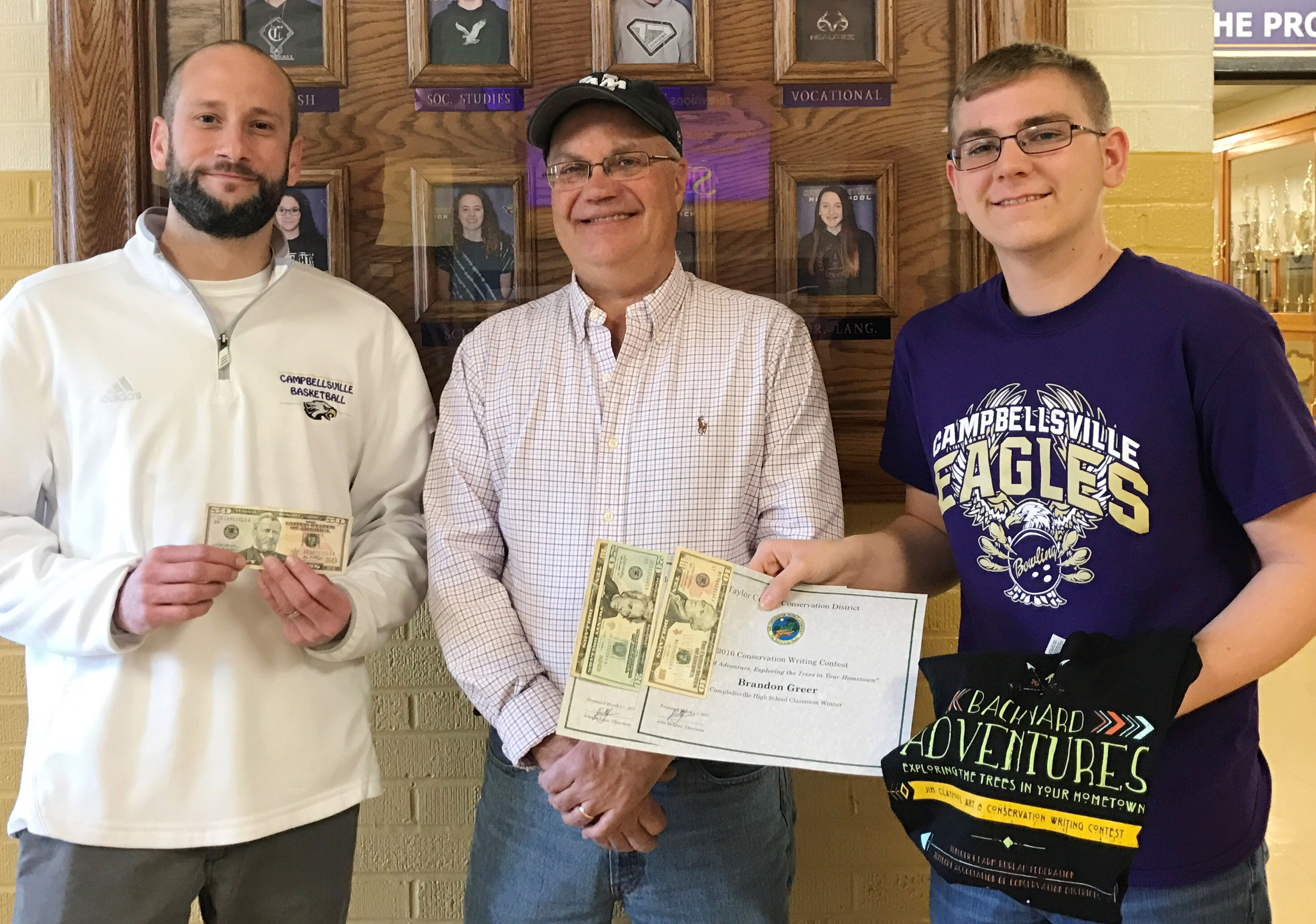 CHS sophomore Brandon Greer, at right, won the writing contest for his school and received his awards from Taylor County Conservation District Board Member Barry Smith, center. Greer's teacher Ben Davis, at left, won a $50 prize.