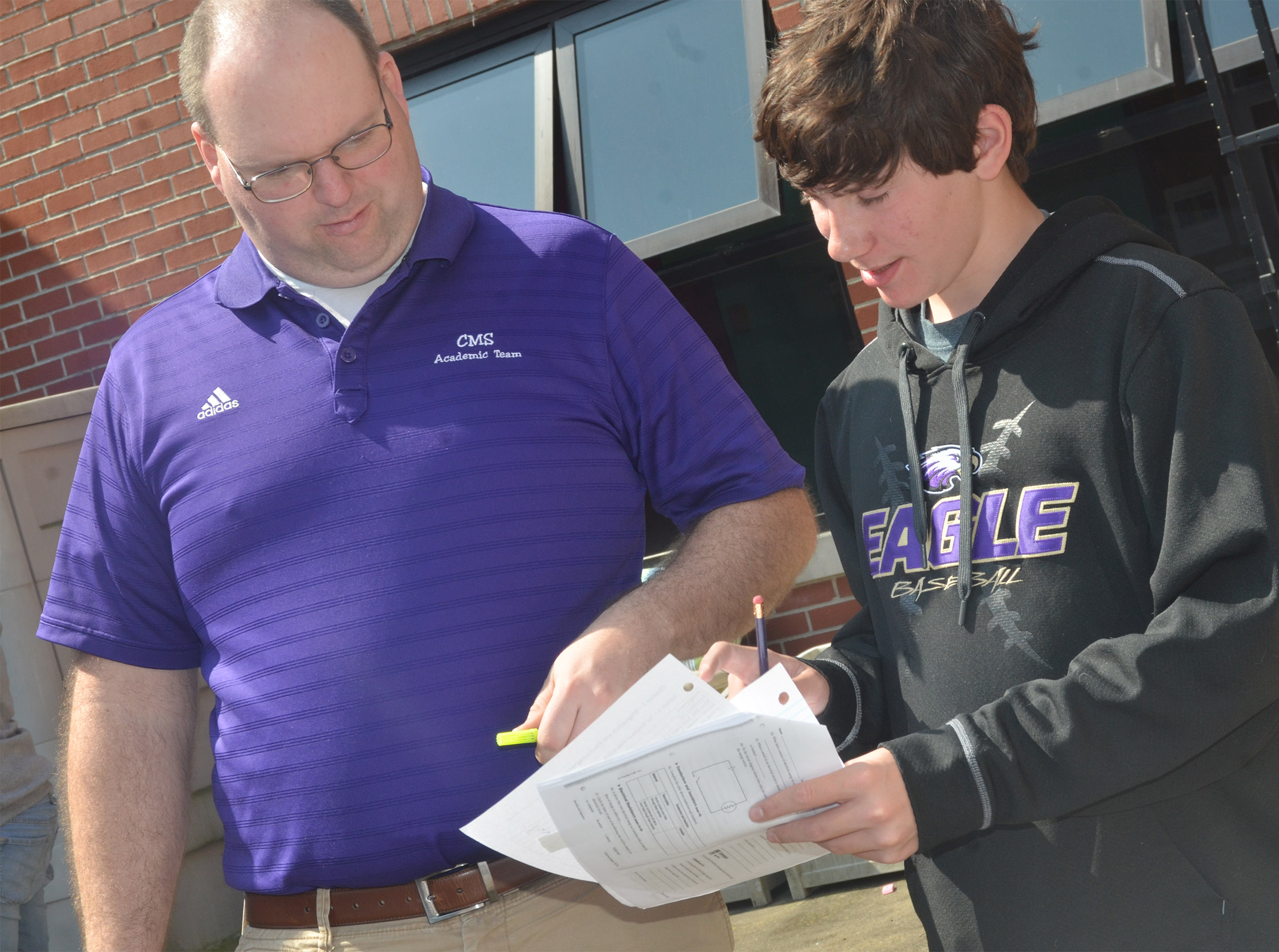 CMS seventh-grade science teacher Steven Gumm helps student Peyton Dabney with a question.