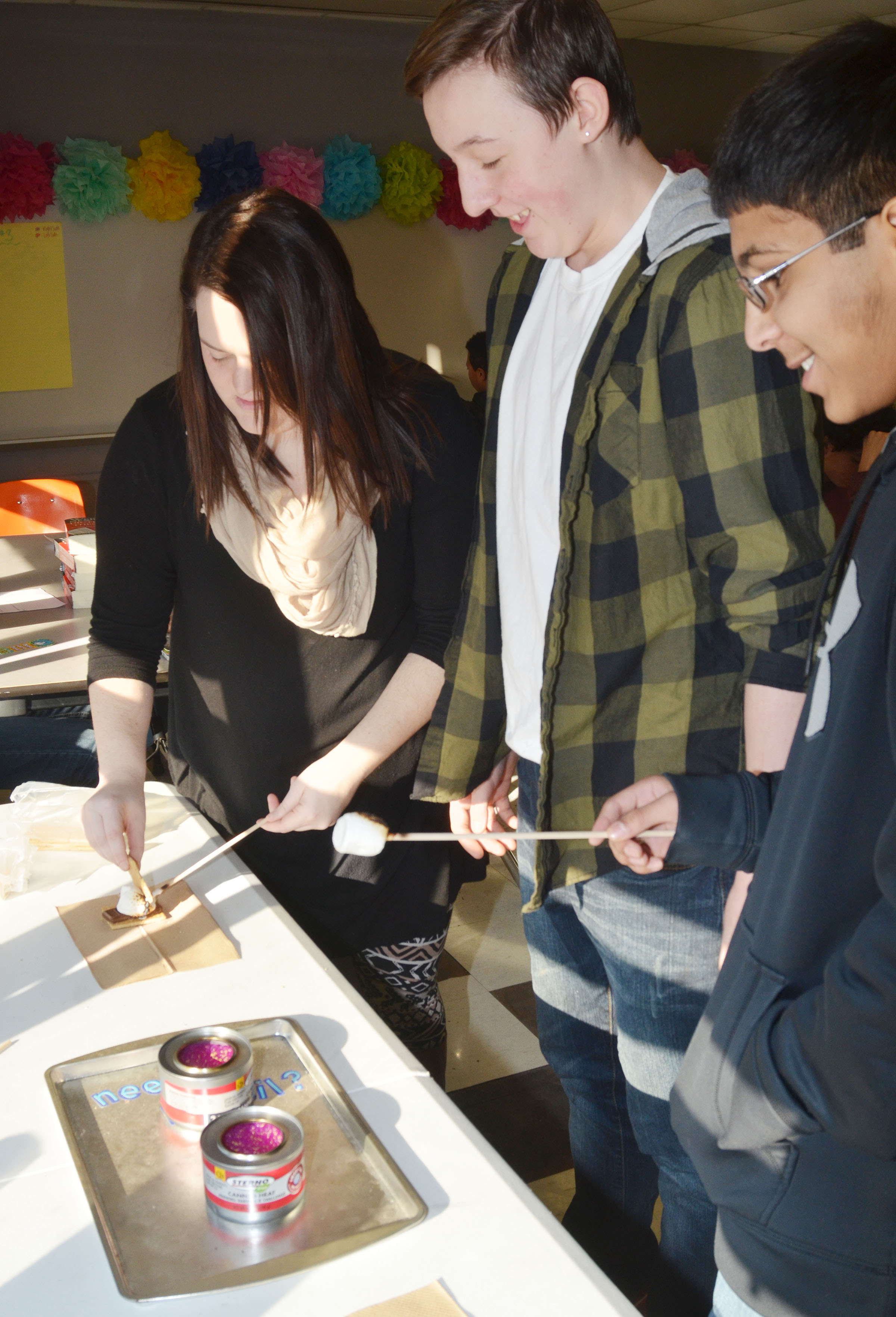CMS eighth-grade language arts teacher Paige Cook, at left, helps students Branson Wilcoxson, center, and Raj Patel make their s'mores.