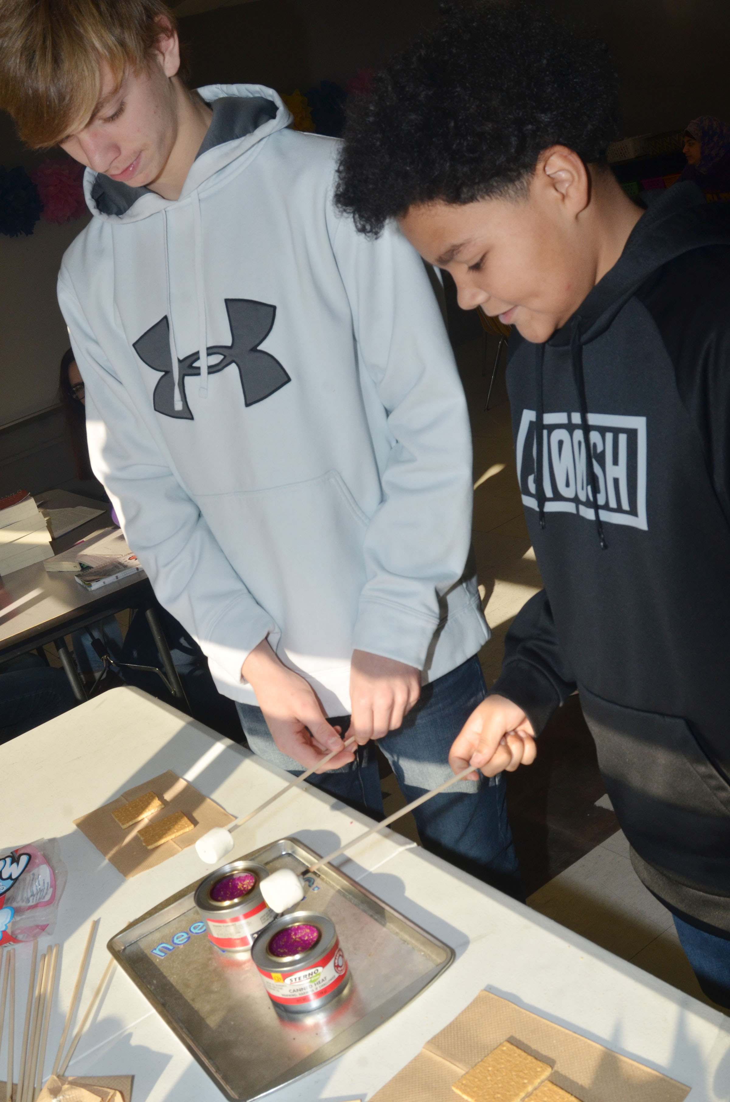 CMS eighth-graders Arren Hash, at left, and Alex Lofton toast their marshmallows.