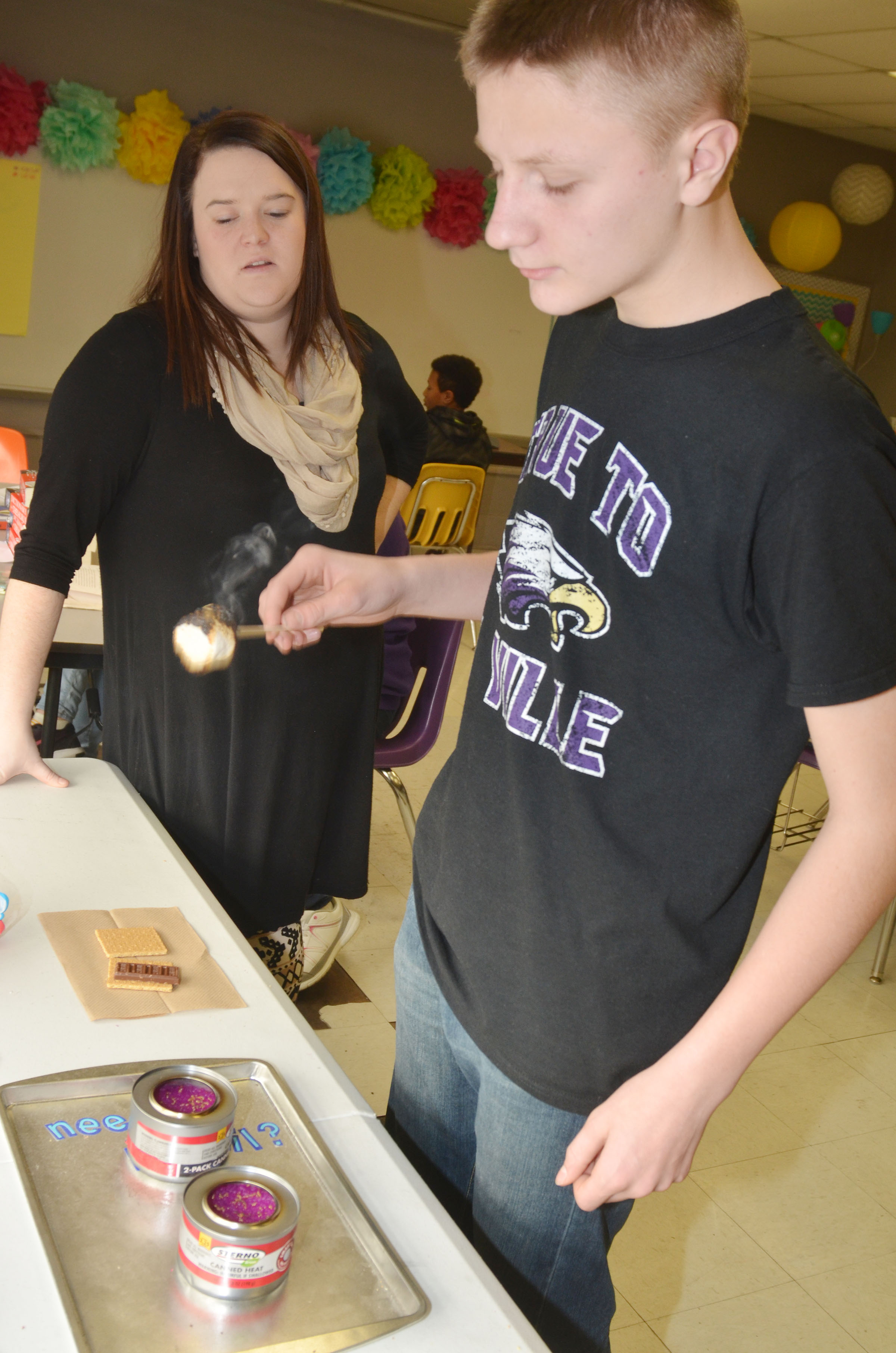 CMS eighth-grader Jake Dicken makes sure his marshmallow is toasted just right, while language arts teacher Paige Cook helps him.