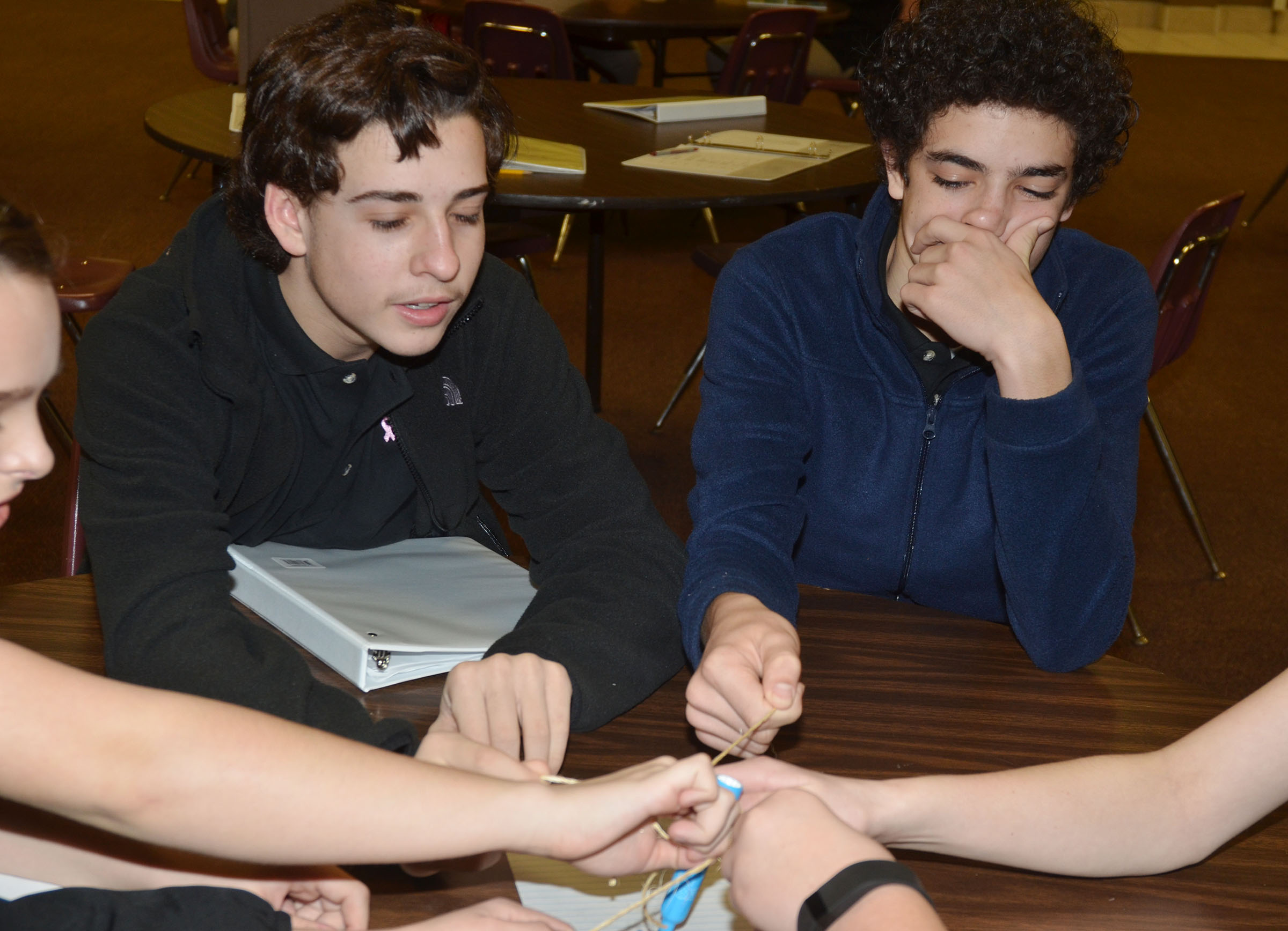 CMS eighth-graders John Orberson, at left, and Kameron Smith participate in the string team-building exercise.