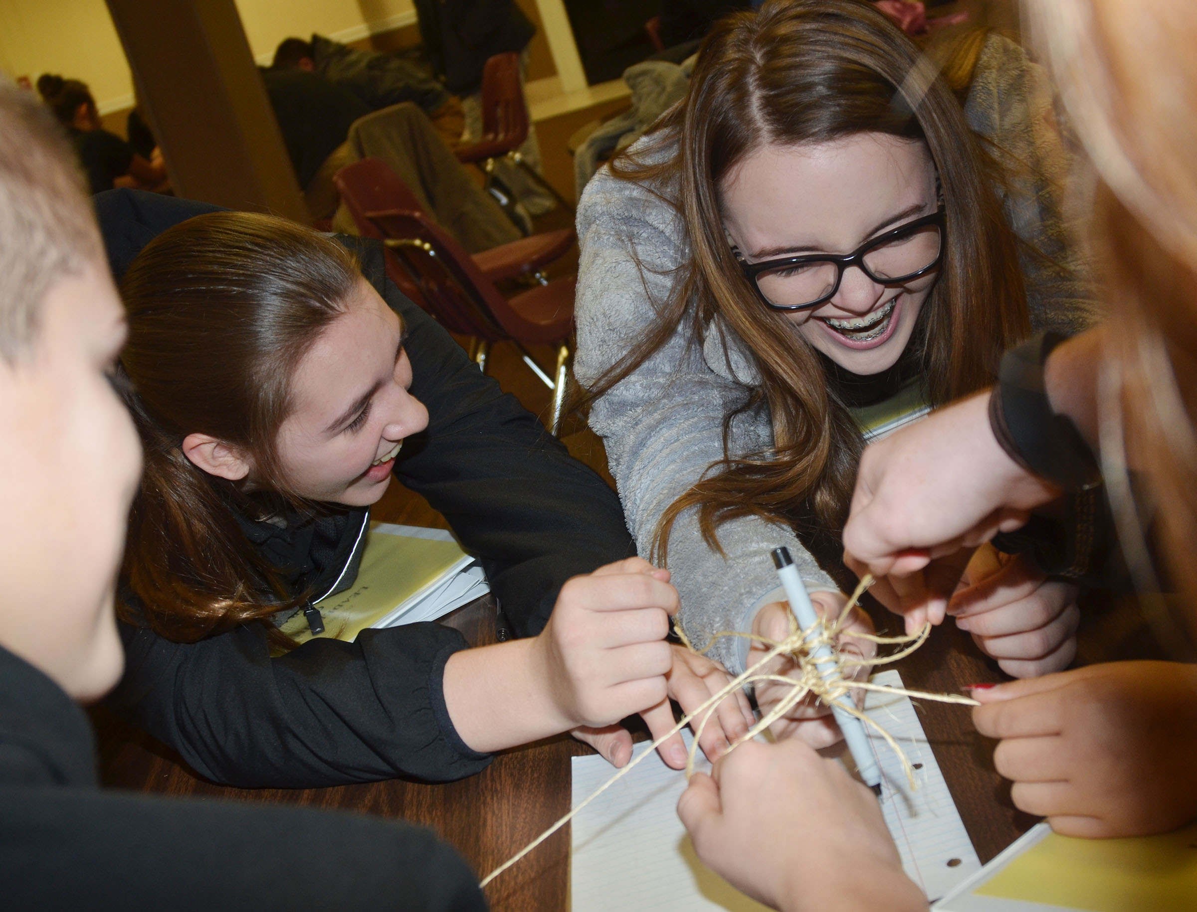 CMS eighth-graders Abi Wiedewitsch, at left, and Kenzi Forbis participate in the string team-building exercise.