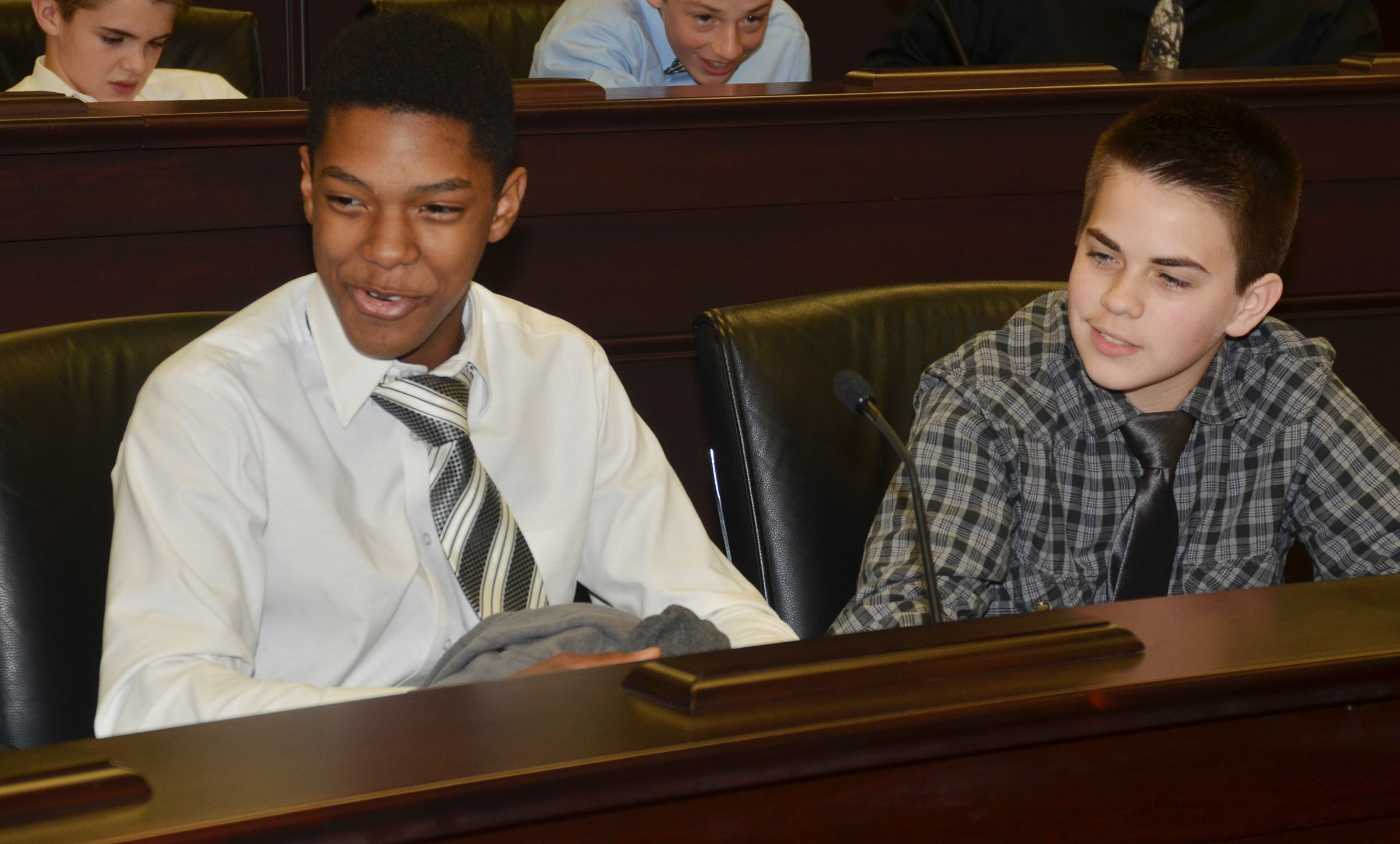 CMS eighth-graders Zaquan Cowan, at left, and Clark Kidwell sit in state representative chairs.