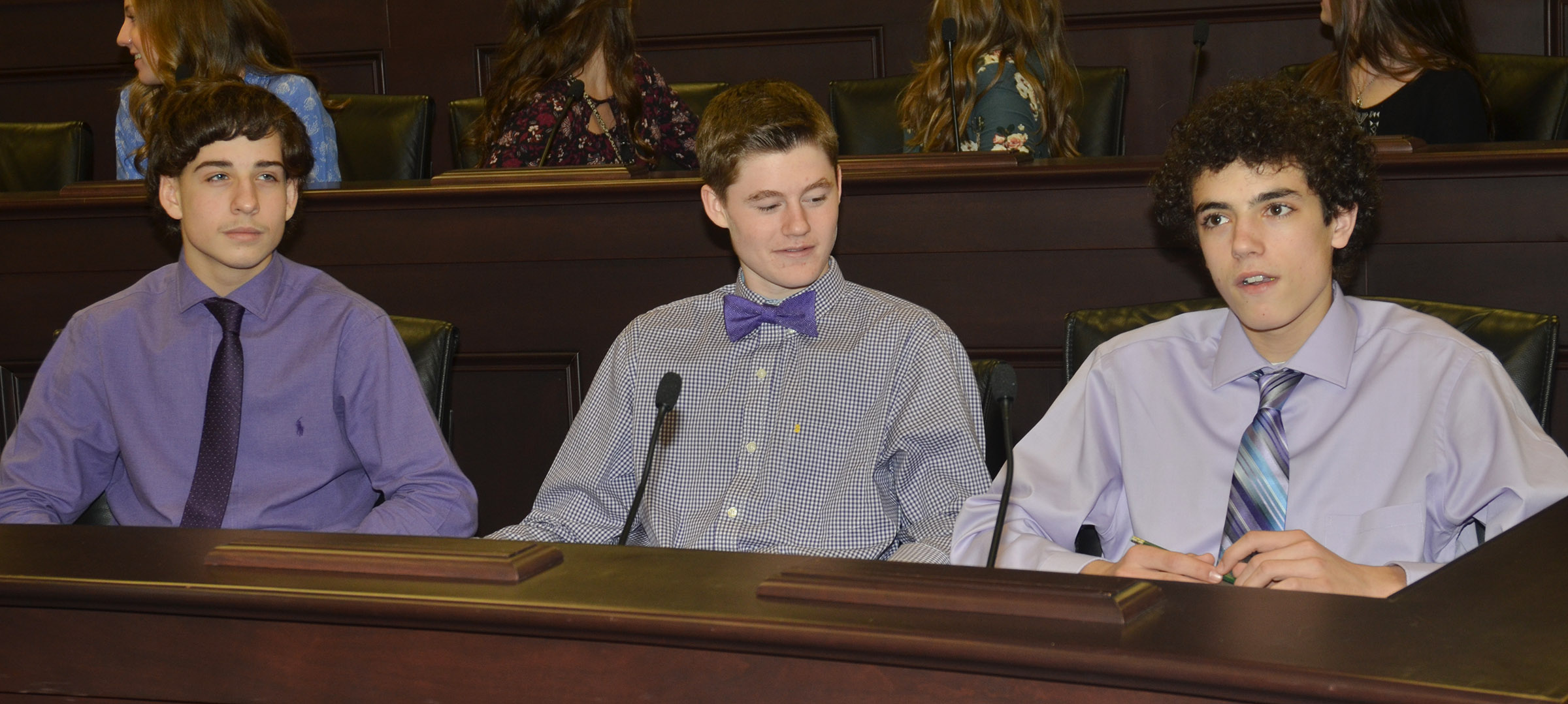 From left, CMS eighth-graders John Orberson, Tristin Faulkner and Kameron Smith sit in state representative chairs.