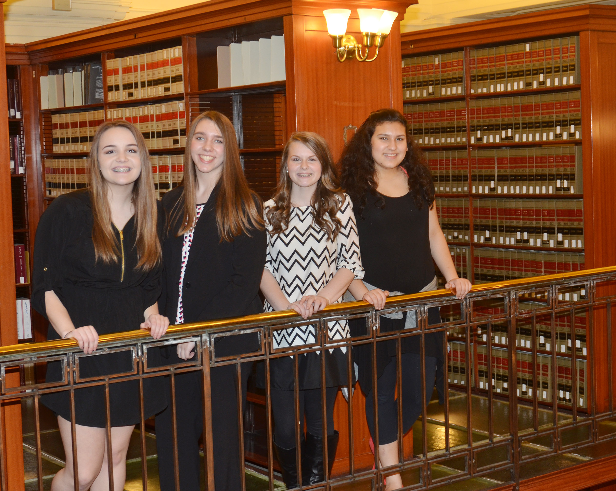 From left, CMS eighth-graders Kenzi Forbis, Abi Wiedewitsch, Taylor Knight and Anna Clara Moura pose for a photo in the capitol library.