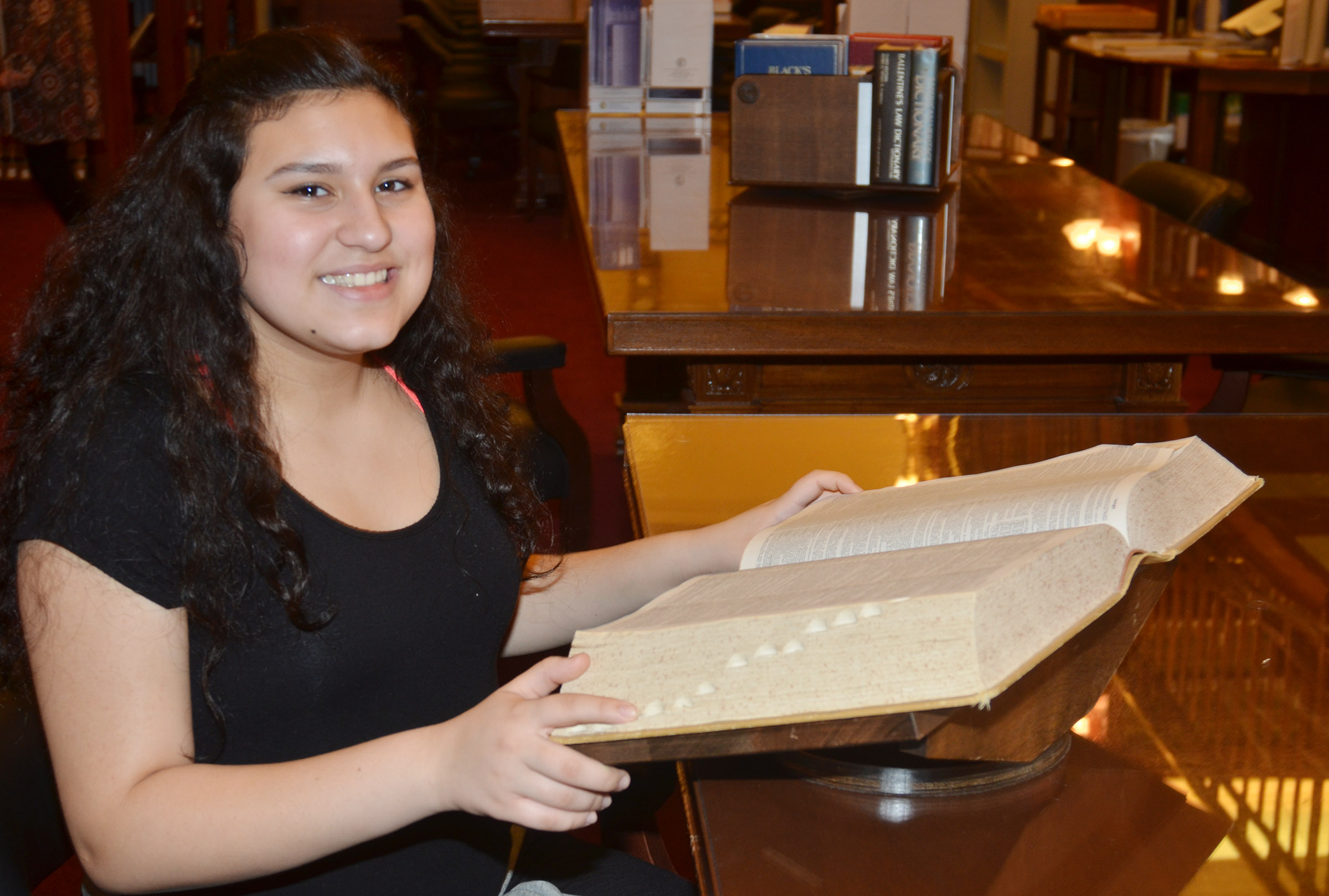 CMS eighth-grader Anna Clara Moura does some reading in the capitol library.