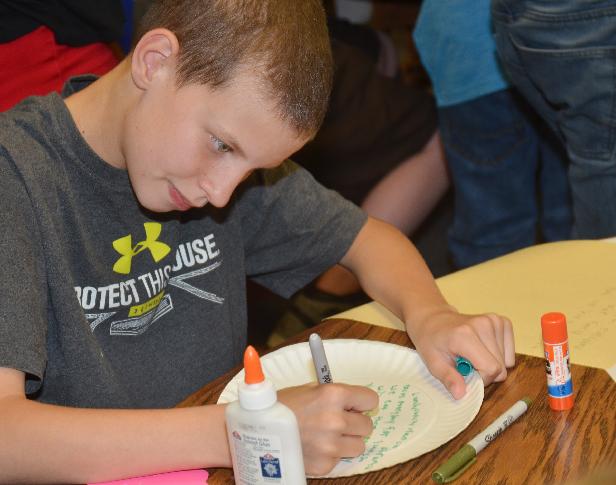 CMS fourth-grader Rowan Petett writes his poem on a paper plate.