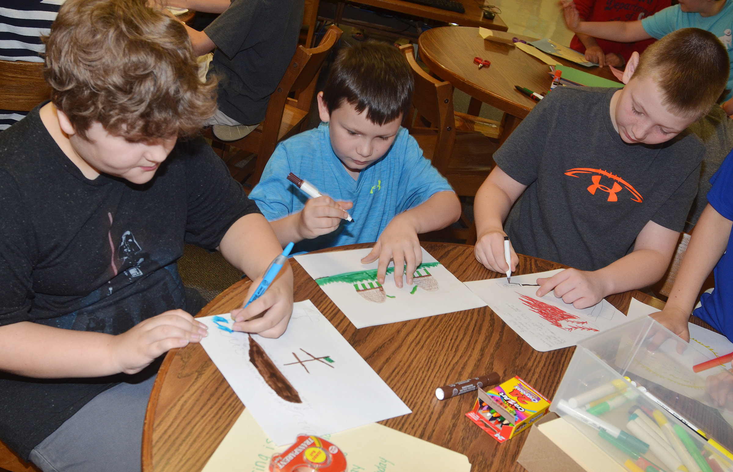 From left, CMS fourth-graders Zeke Harris, Mason Fisher and Kaleb Miller illustrate their poems.