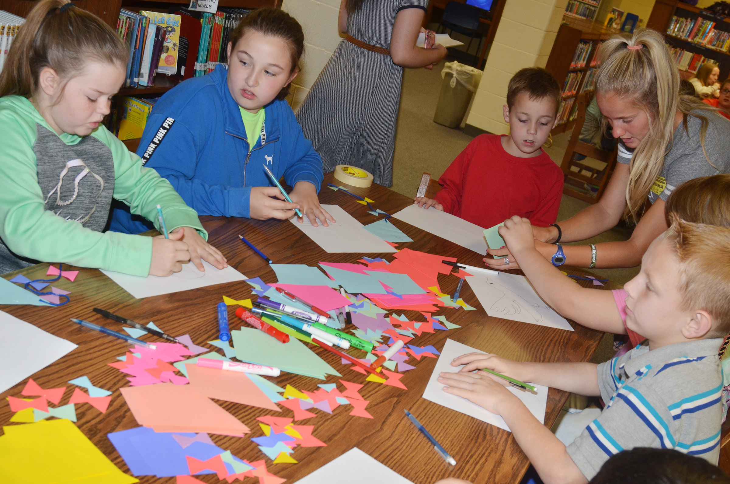 CMS fourth-graders, from left, Miley Hash, Riley Newton and Spencer Bates work on their free verse poems with their classmates.