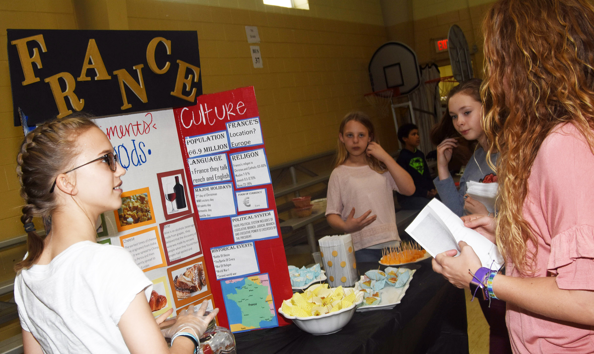CMS sixth-graders Chloe Thompson, at left, and Gabby Bright present food commonly found in France.