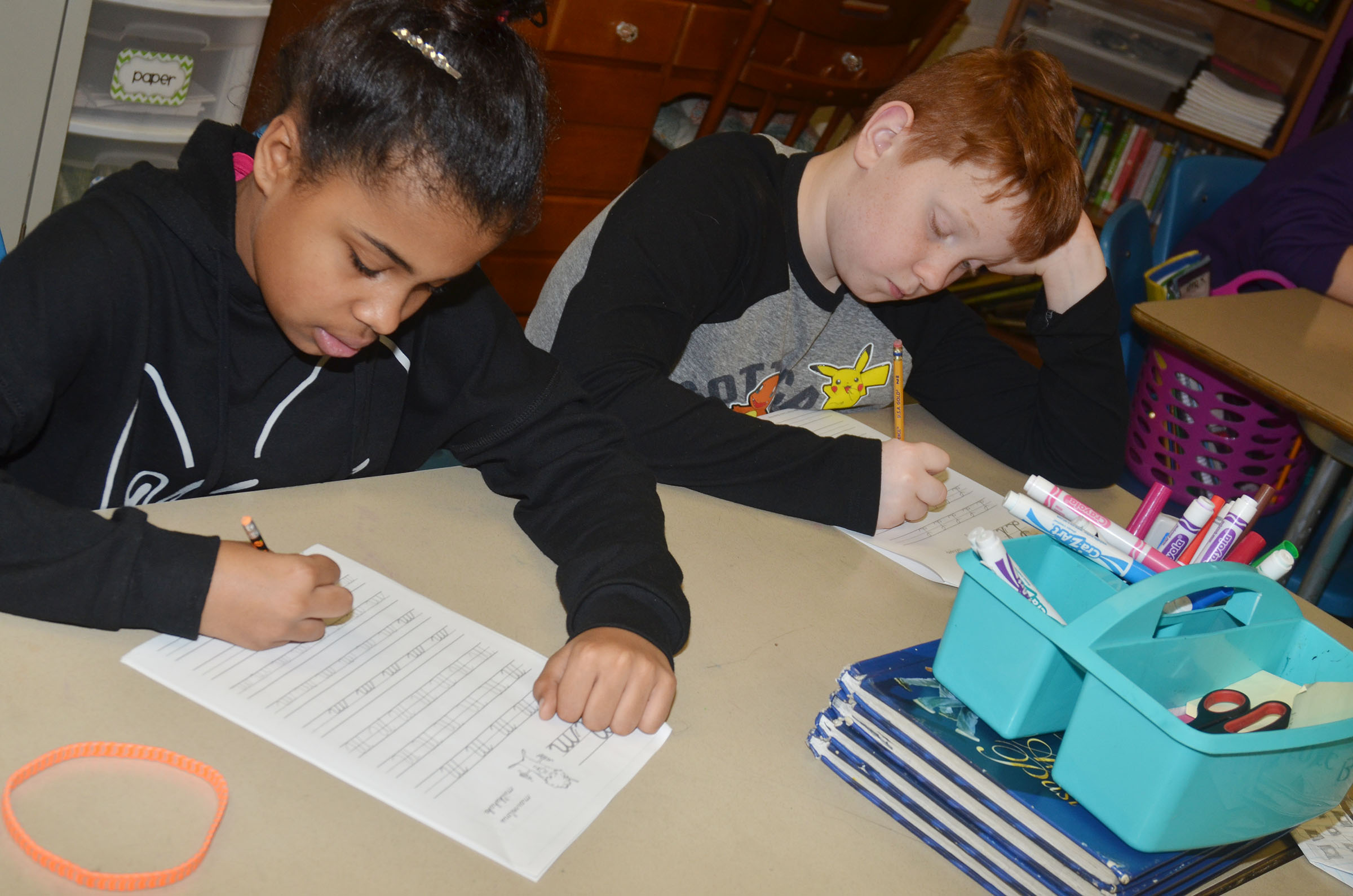 CMS fifth-graders Kendra Coulter, at left, and Conner Rinehart practice cursive writing.