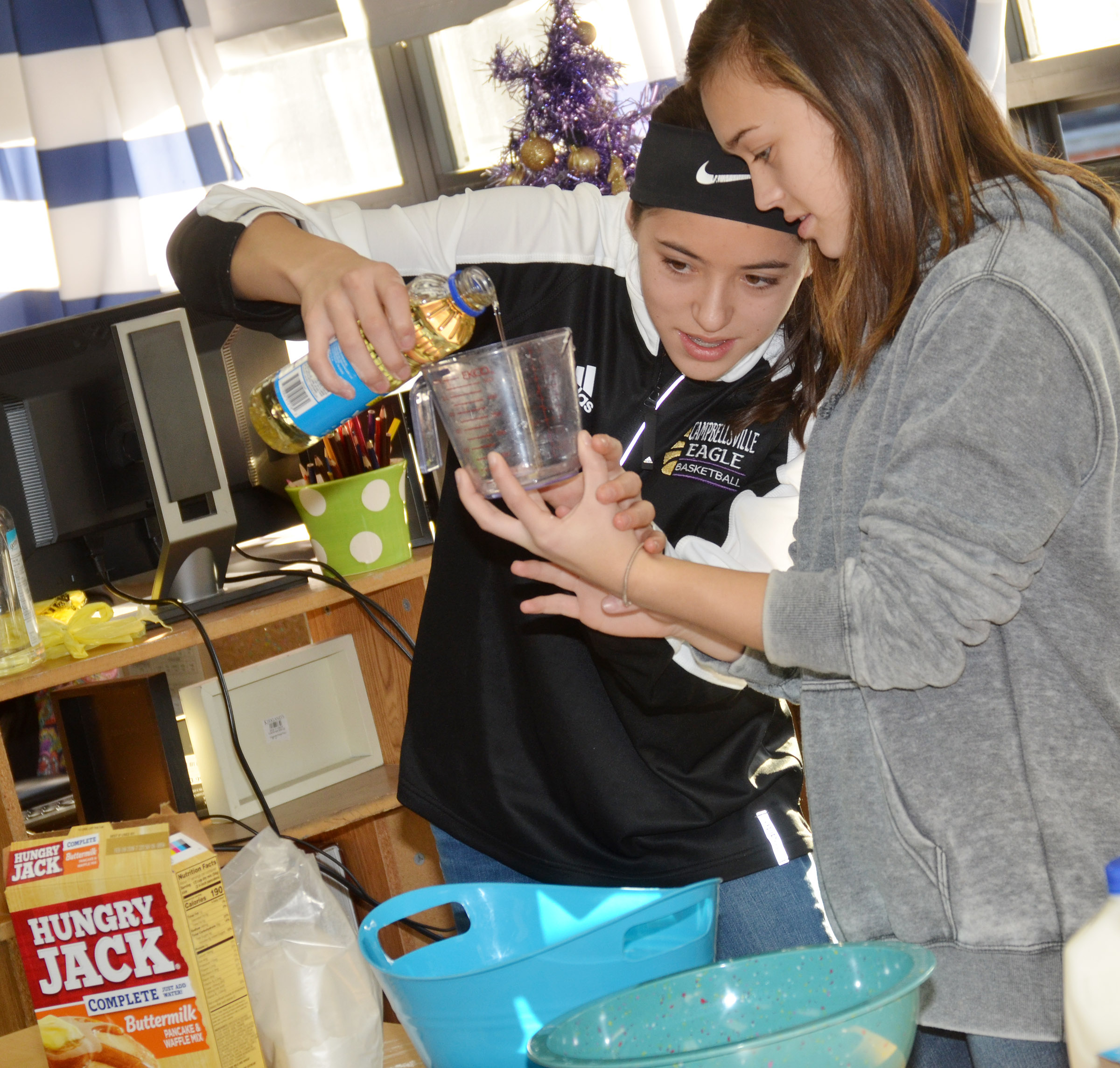 CMS eighth-graders Kaylyn Smith, at left, and Tayler Thompson demonstrate how to make waffles.