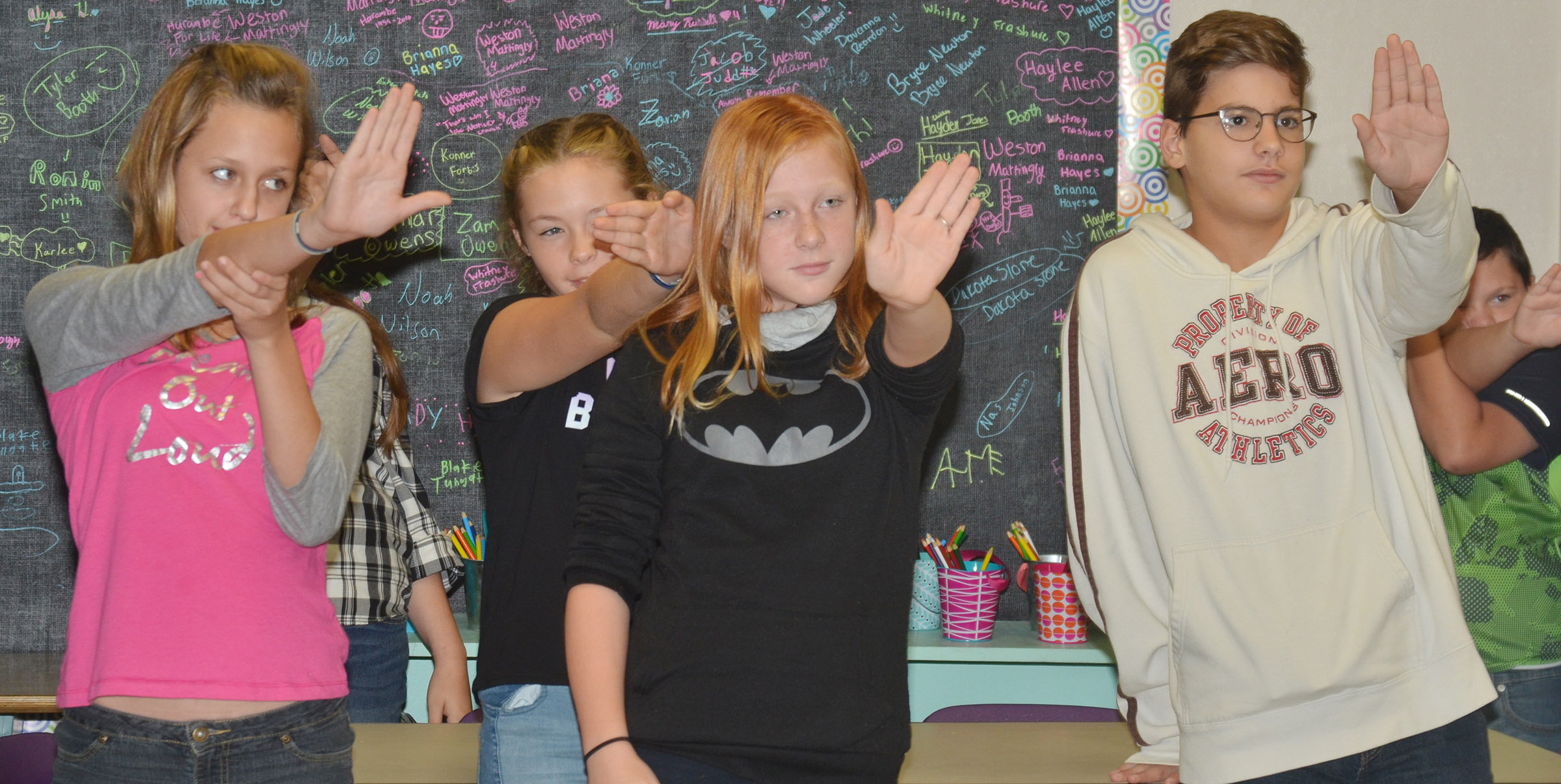 CMS sixth-graders, from left, Halley Wooley, CheyAnn Edwards, Kaydence Wethington and Dalton Morris simulate what an eclipse might look like.