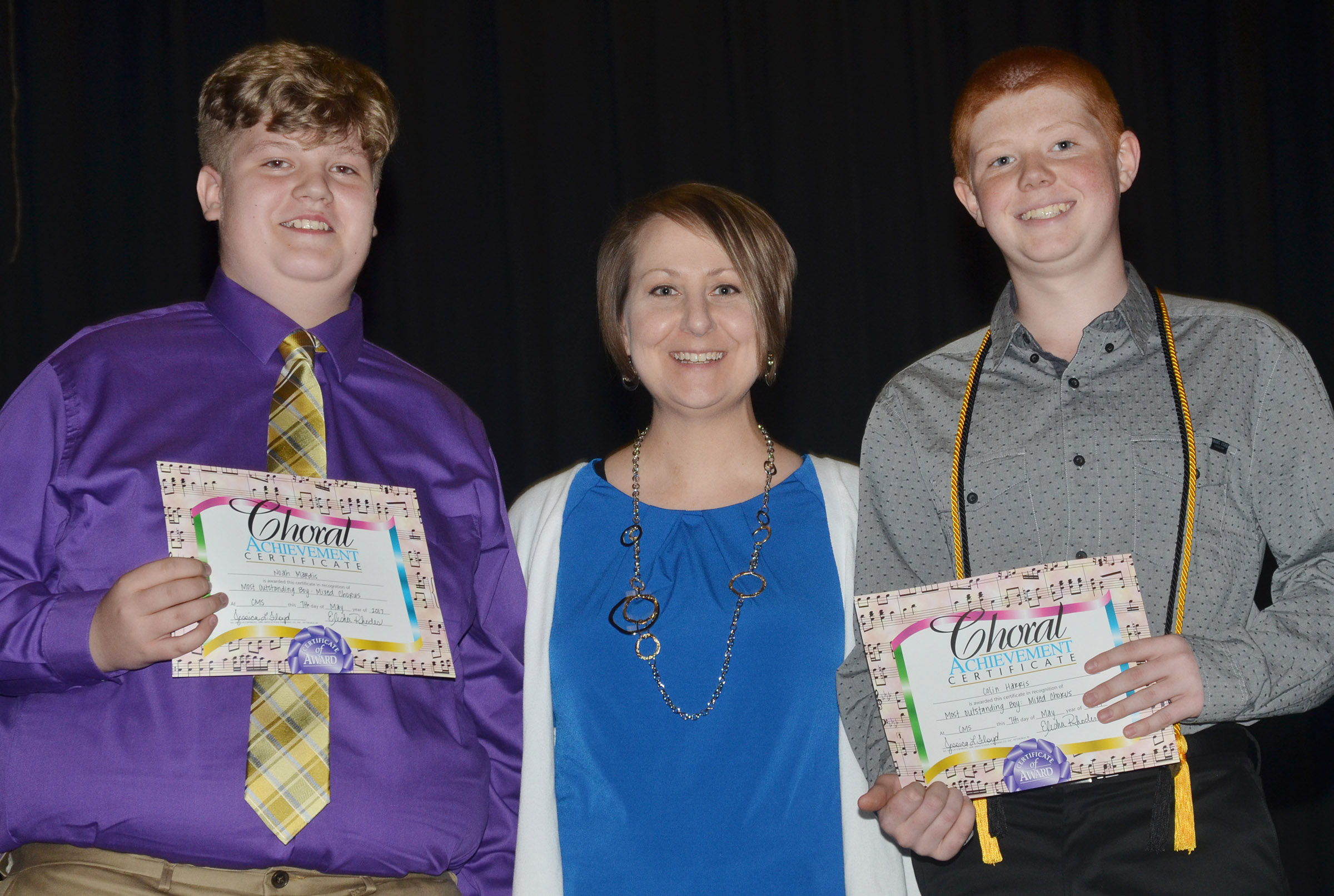 CMS eighth-graders Noah Mardis, at left, and Colin Harris receive the outstanding chorus award from Jessica Floyd.