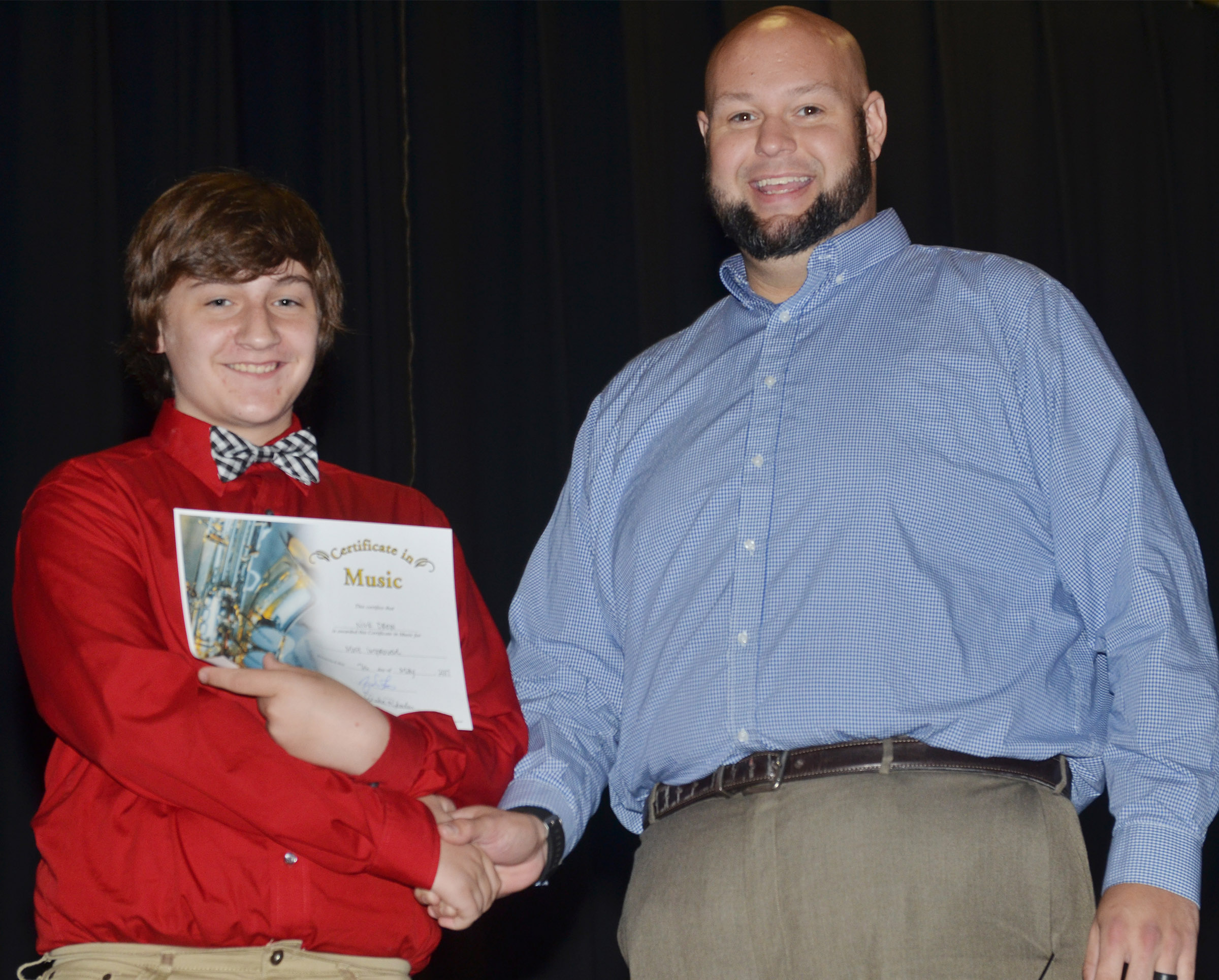 CMS eighth-grader Nick Drew receives the most improved music award from teacher Zach Shelton.