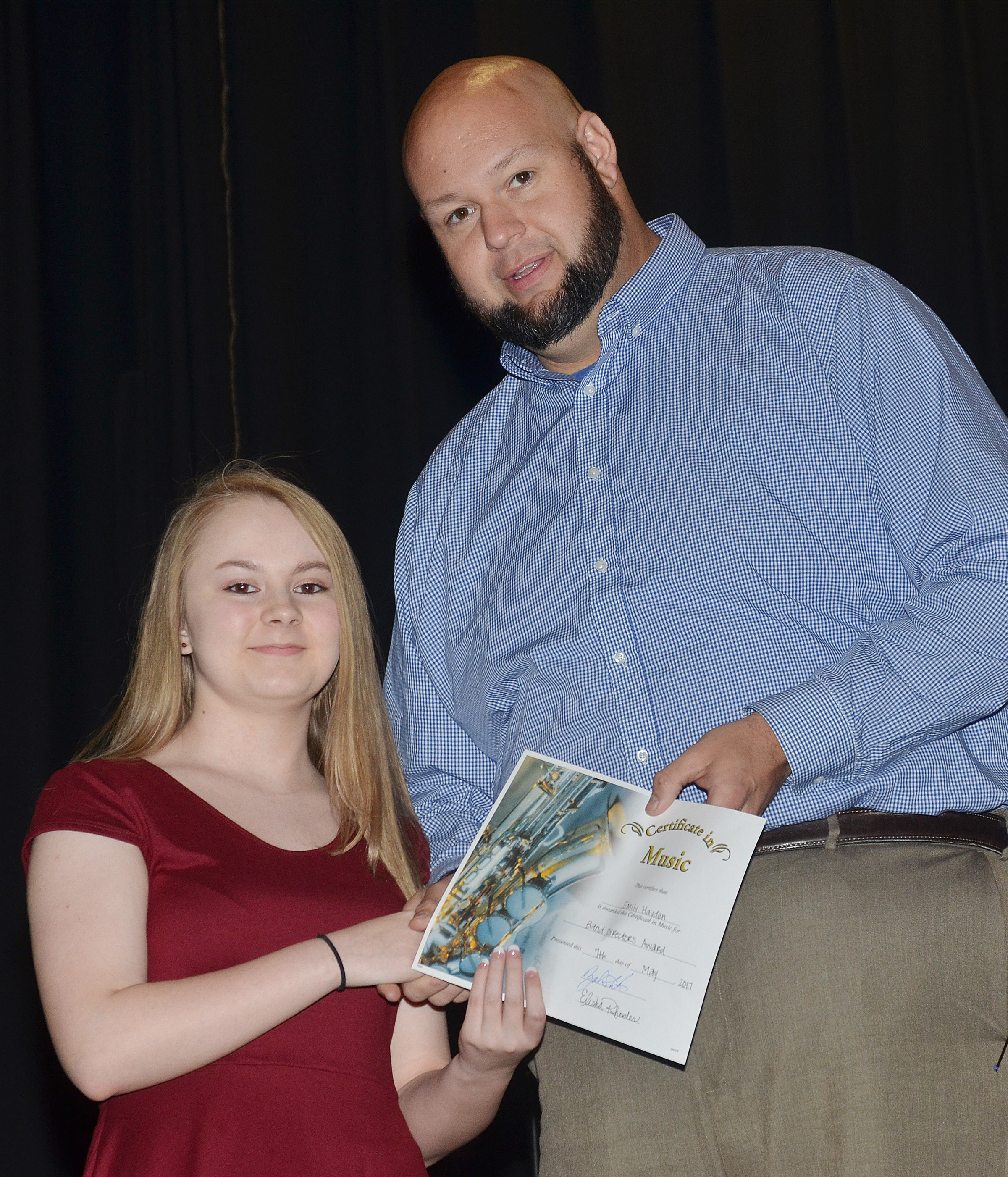 CMS eighth-grader Emily Hayden receives the band director's award from teacher Zach Shelton.