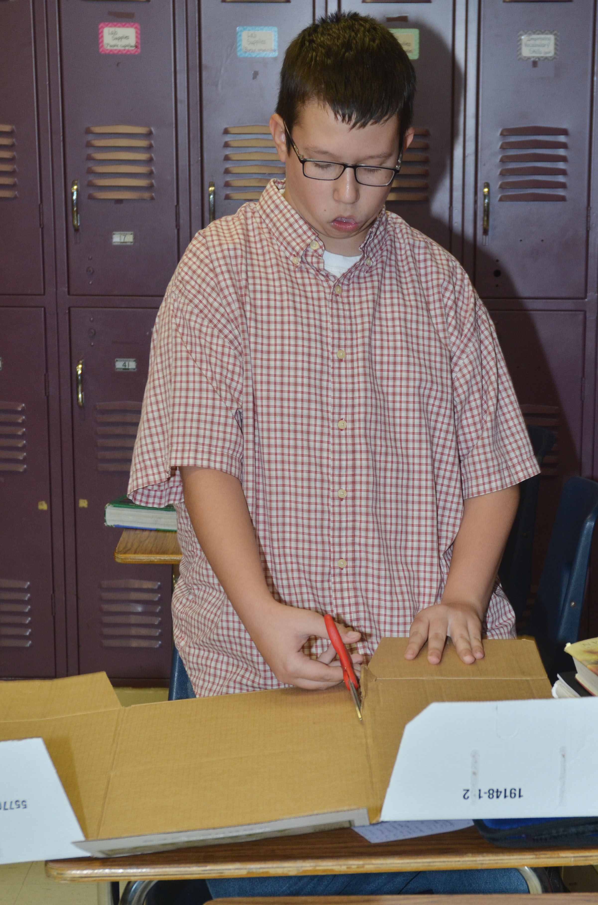 CMS eighth-grader Nathan Sowders cuts his box.