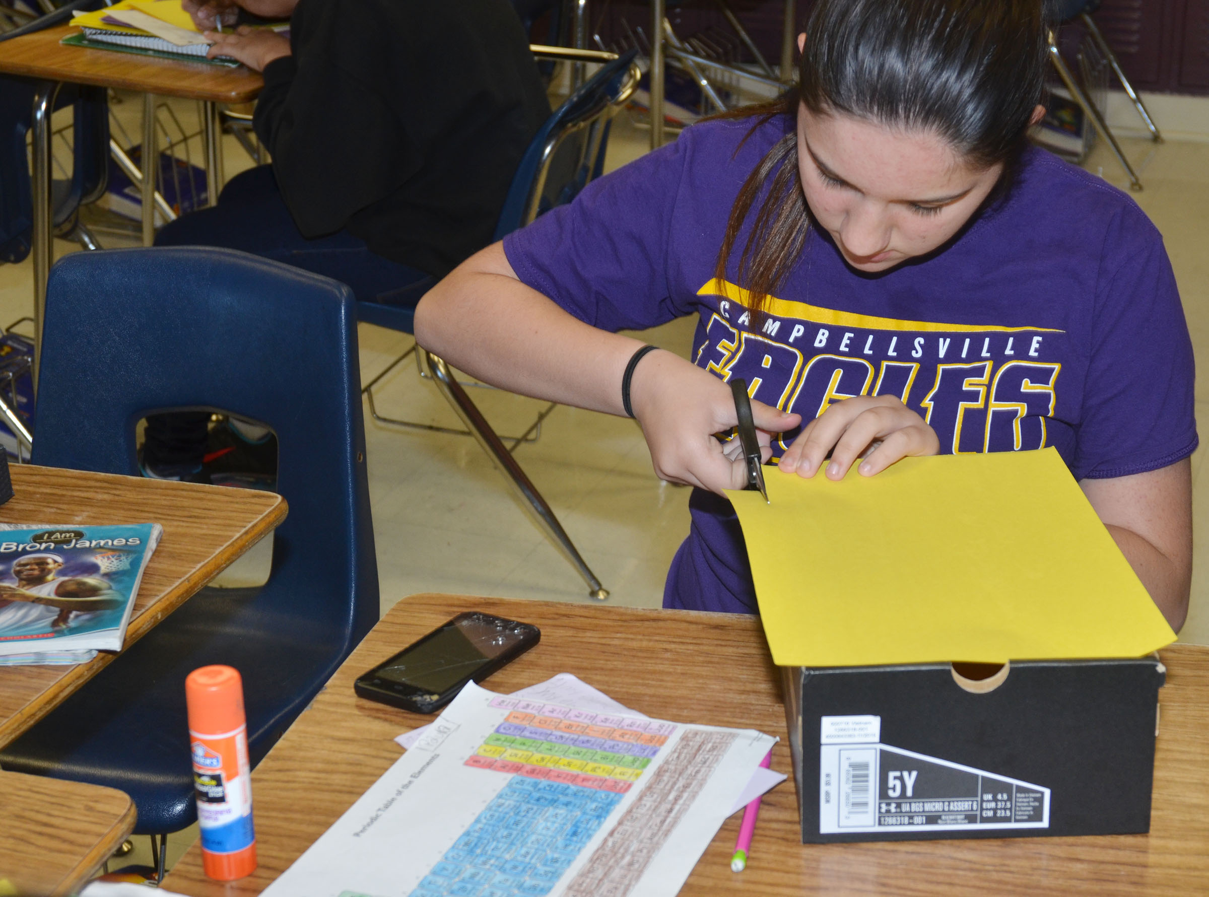CMS eighth-grader Paula Hoskins cuts out construction paper for her element box.