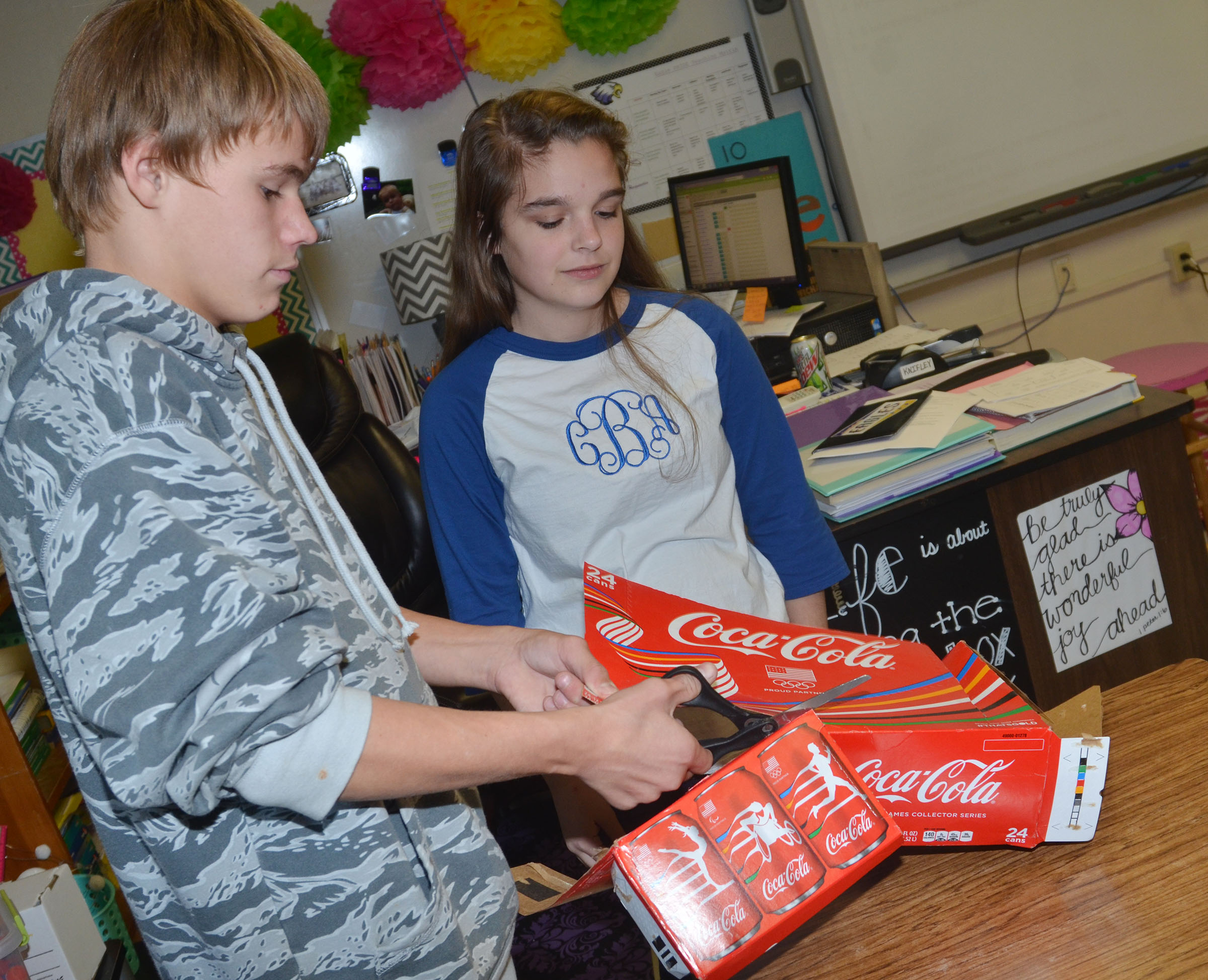 CMS eighth-graders Dalton Reynolds, at left, and Chloe Bennett cut a box to make their element boxes.