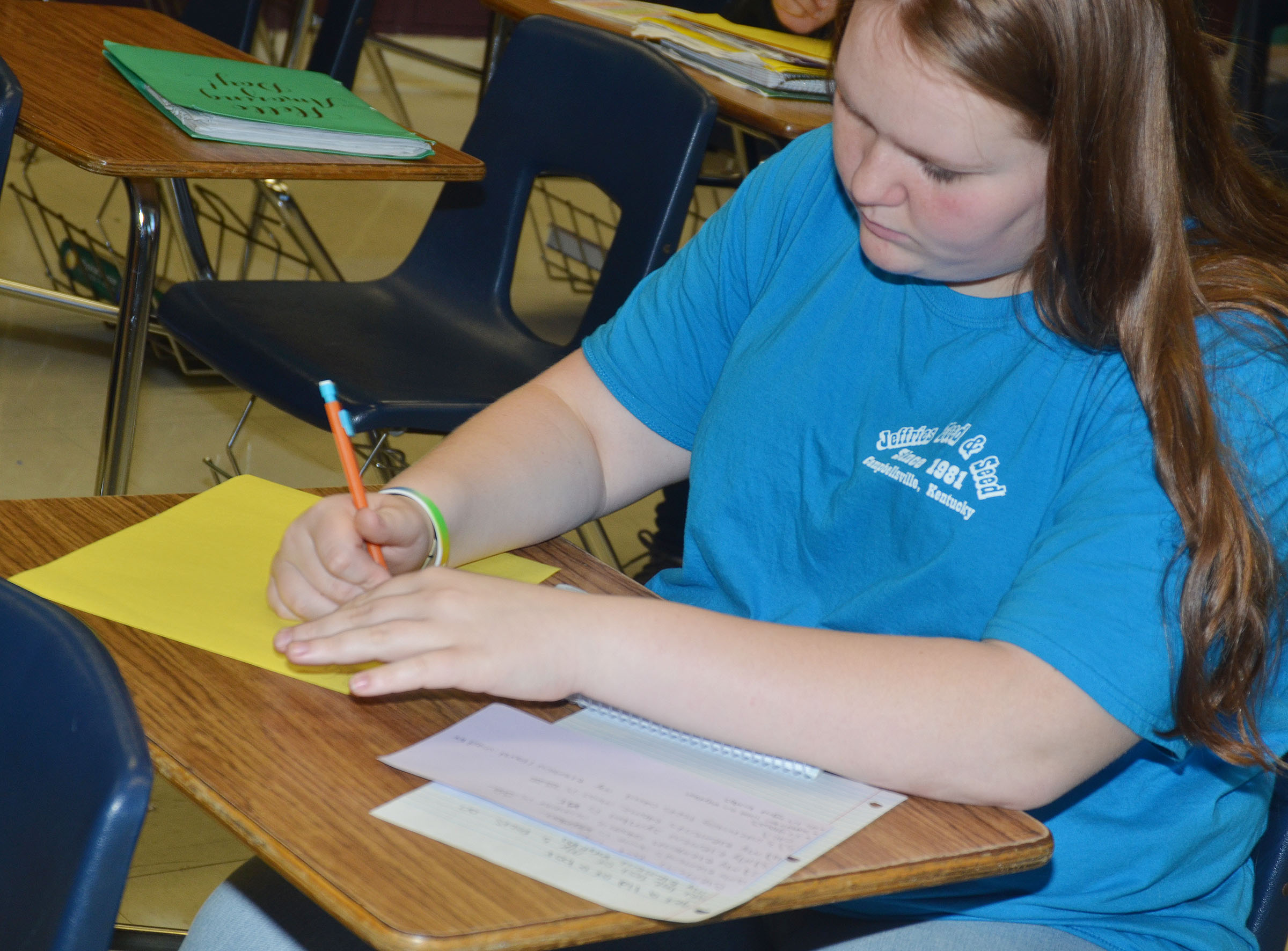 CMS eighth-grader Trinity Lobb uses her research to write information about her element on construction paper.