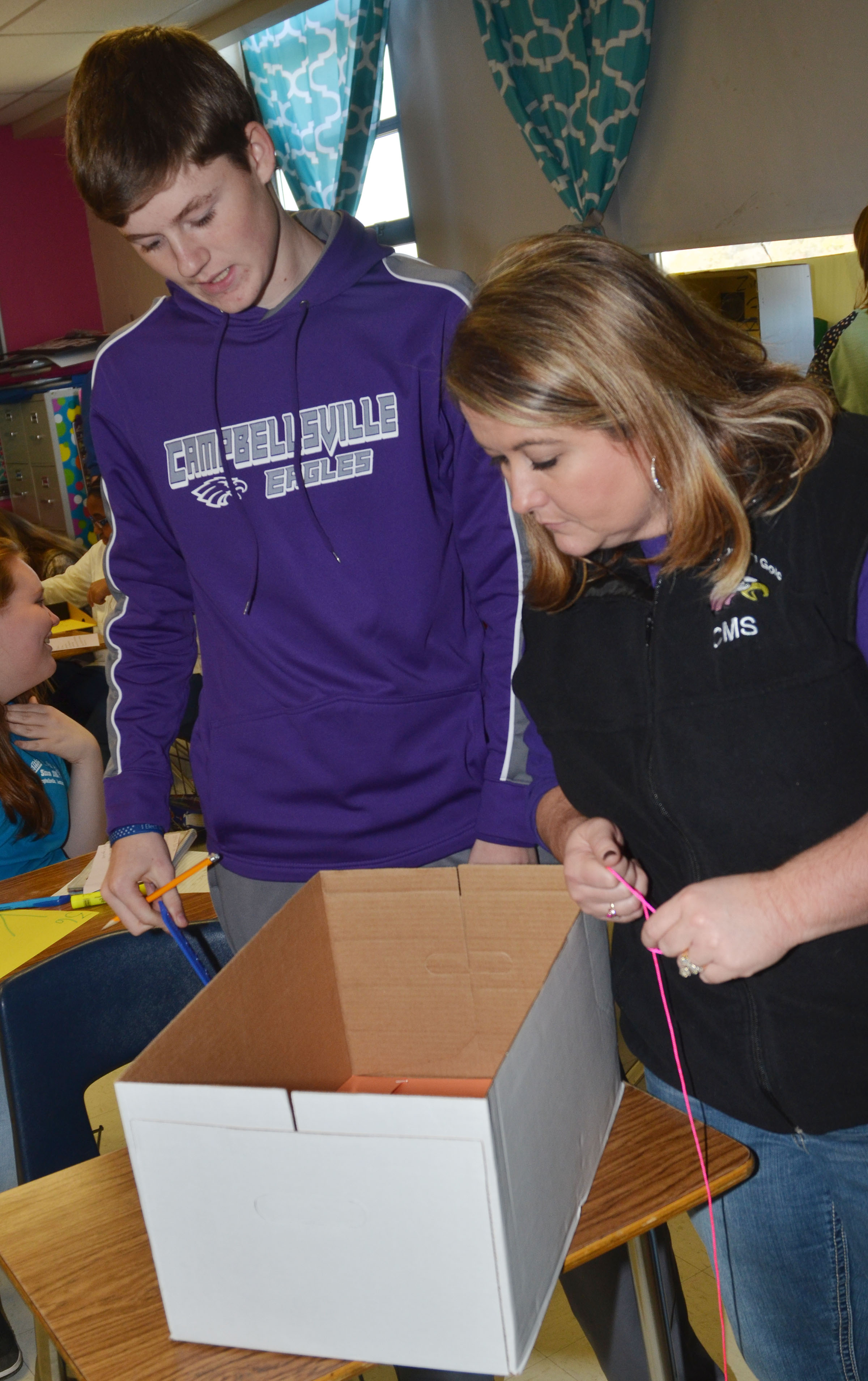 CMS eighth-grade teacher Amy Knifley helps Tristin Faulkner with his element box.