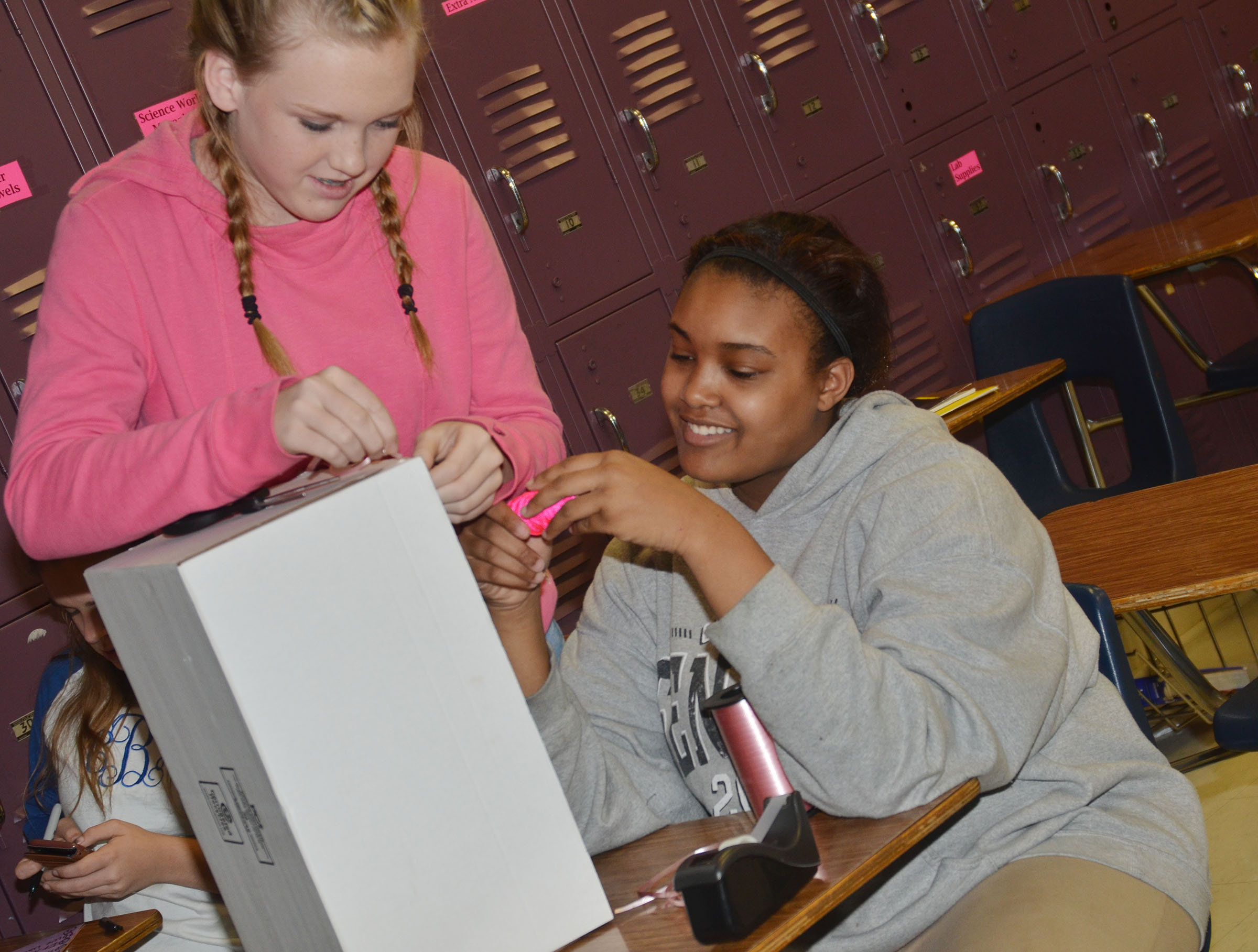 CMS eighth-graders Catlyn Clausen, at left, and Kelsey King add decorations to an element box.