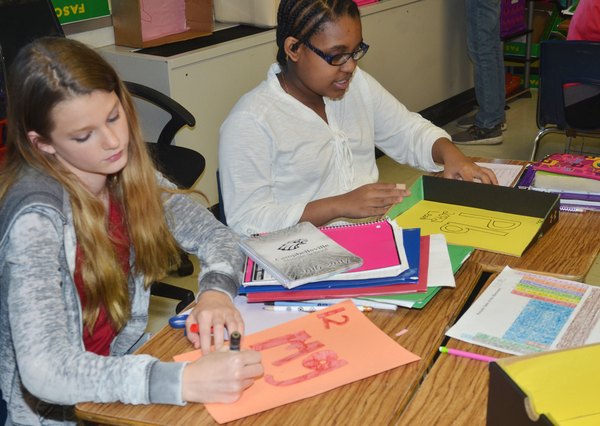 CMS eighth-graders Katelyn Coffman, at left, and Jasmine Mitchell write information about their elements.