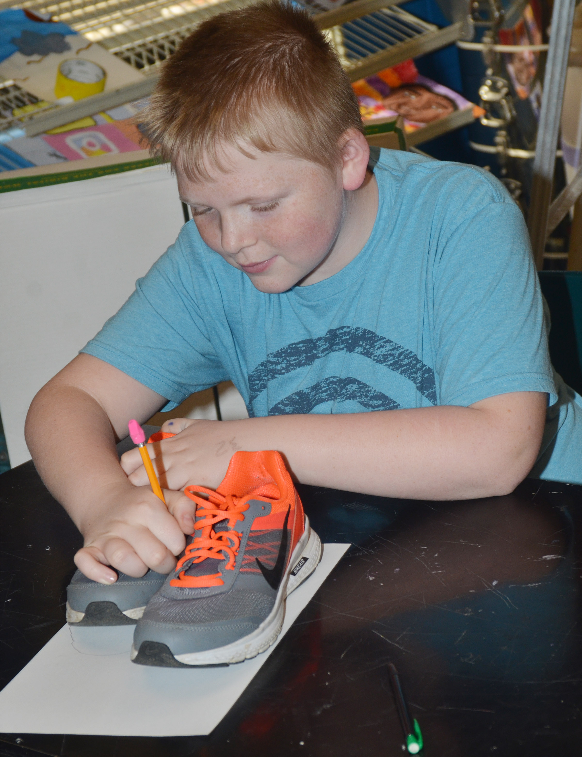 CMS fourth-grader Simon Wilkerson traces his shoes so he can draw himself using the foreshortening technique.