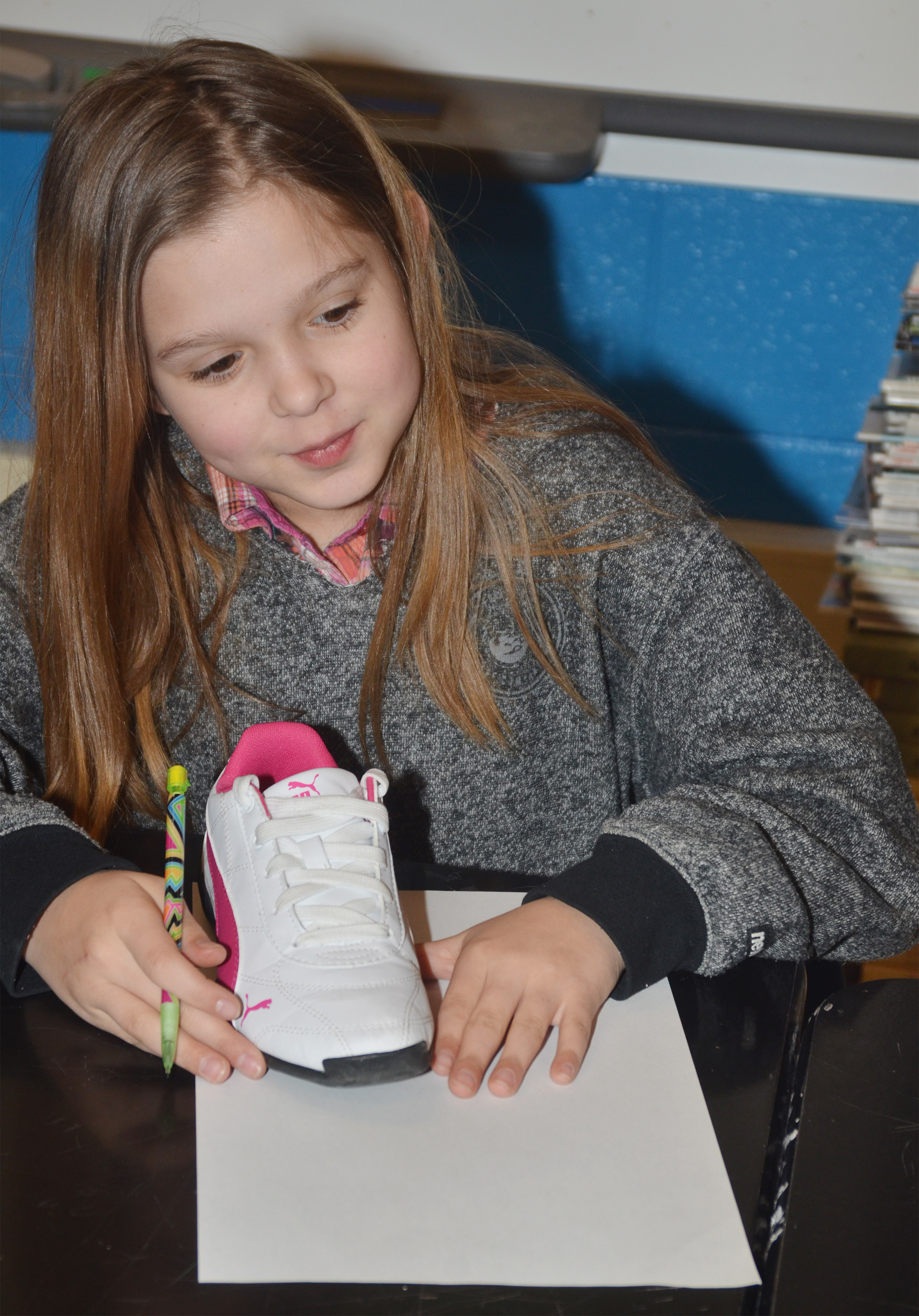 CMS fourth-grader Natasha Torres traces her shoe so she draw herself using the foreshortening technique.