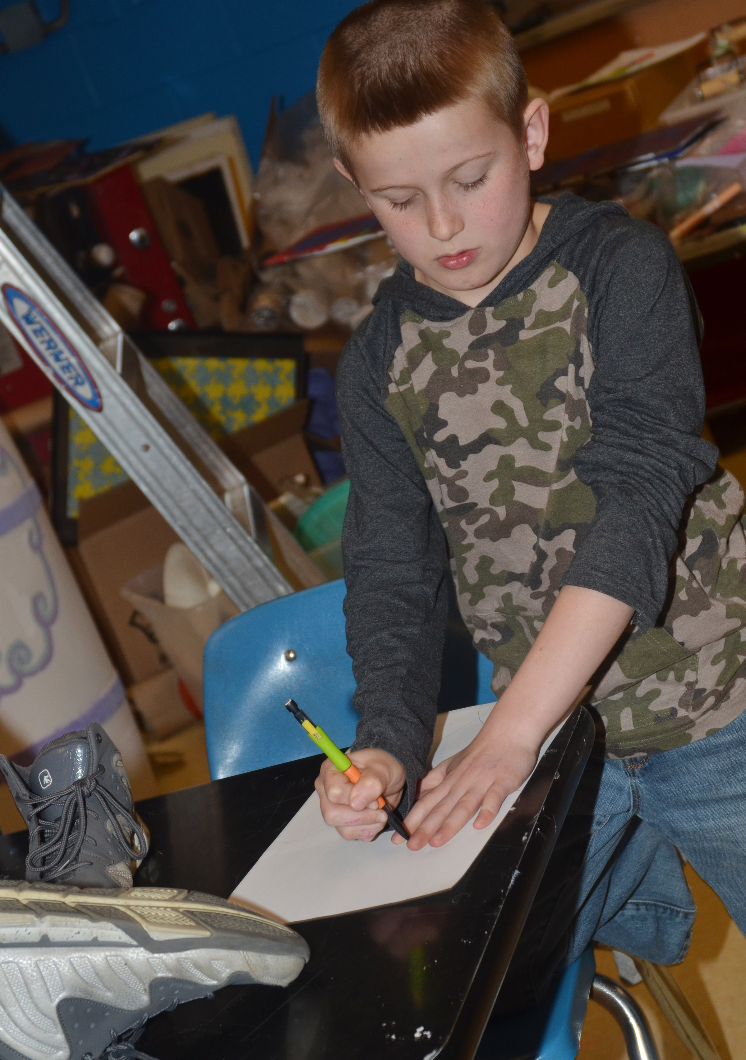 CMS fourth-grader Arthur Singleton traces his hands to draw himself using the foreshortening technique.