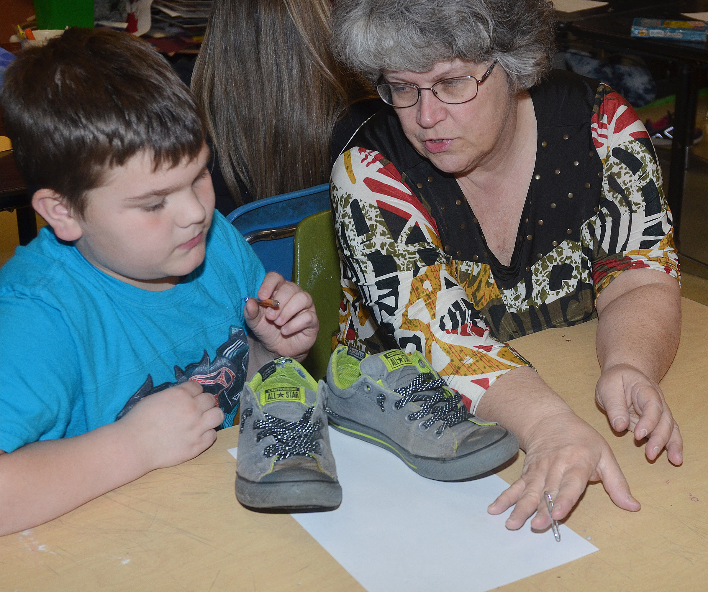 CMS art teacher Jo Ann Harris talks to fourth-grader Logan England about drawing himself using the foreshortening technique.