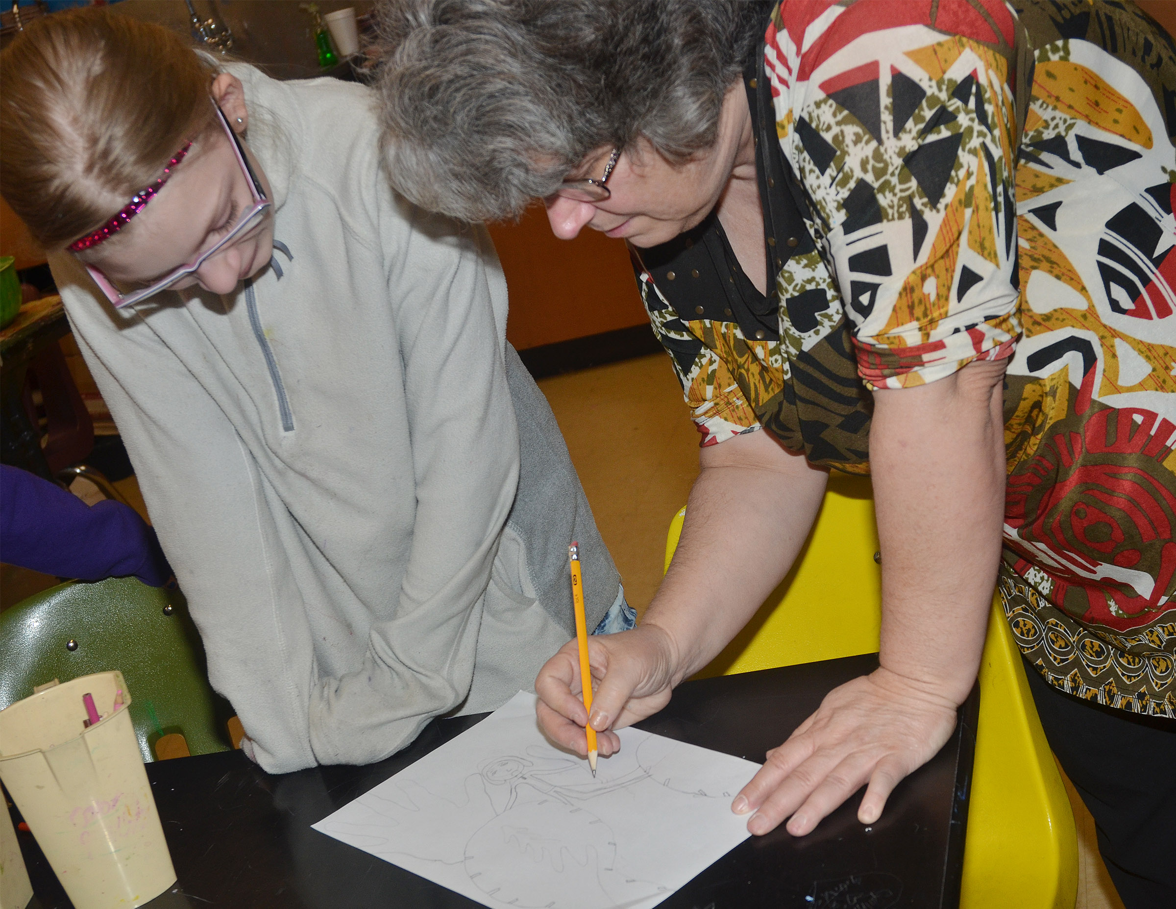 CMS art teacher Jo Ann Harris helps fourth-grader Payton Releford draw herself using the foreshortening technique.
