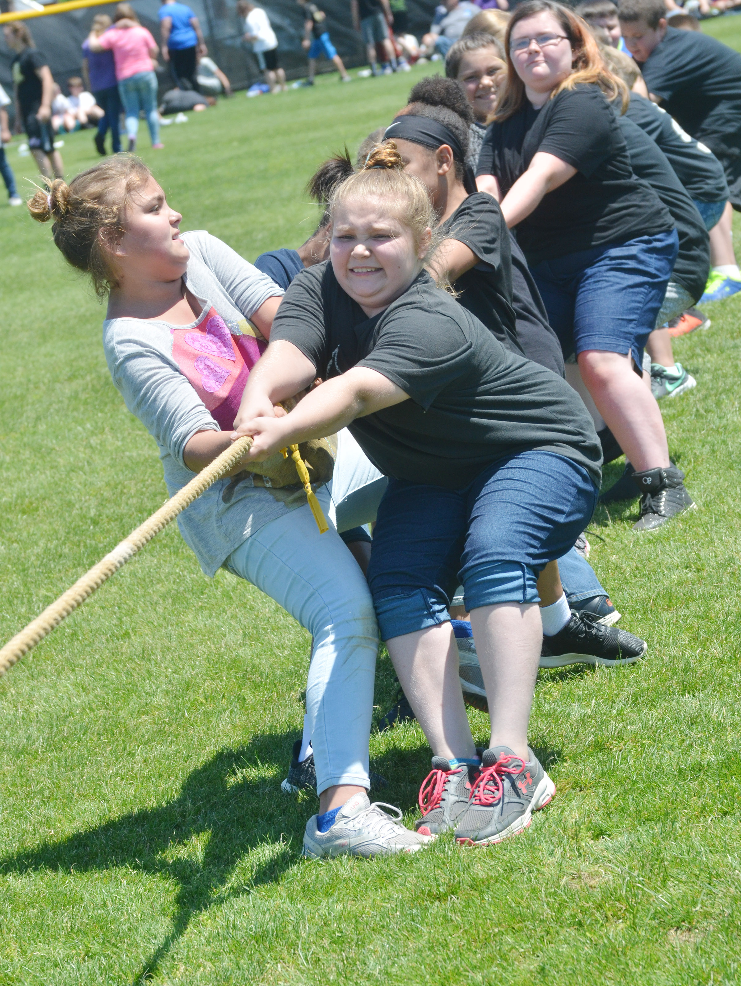 CMS fifth-graders Brooklyn Mays, at left, and Donna Schweickert lead their team in a tug of war battle.