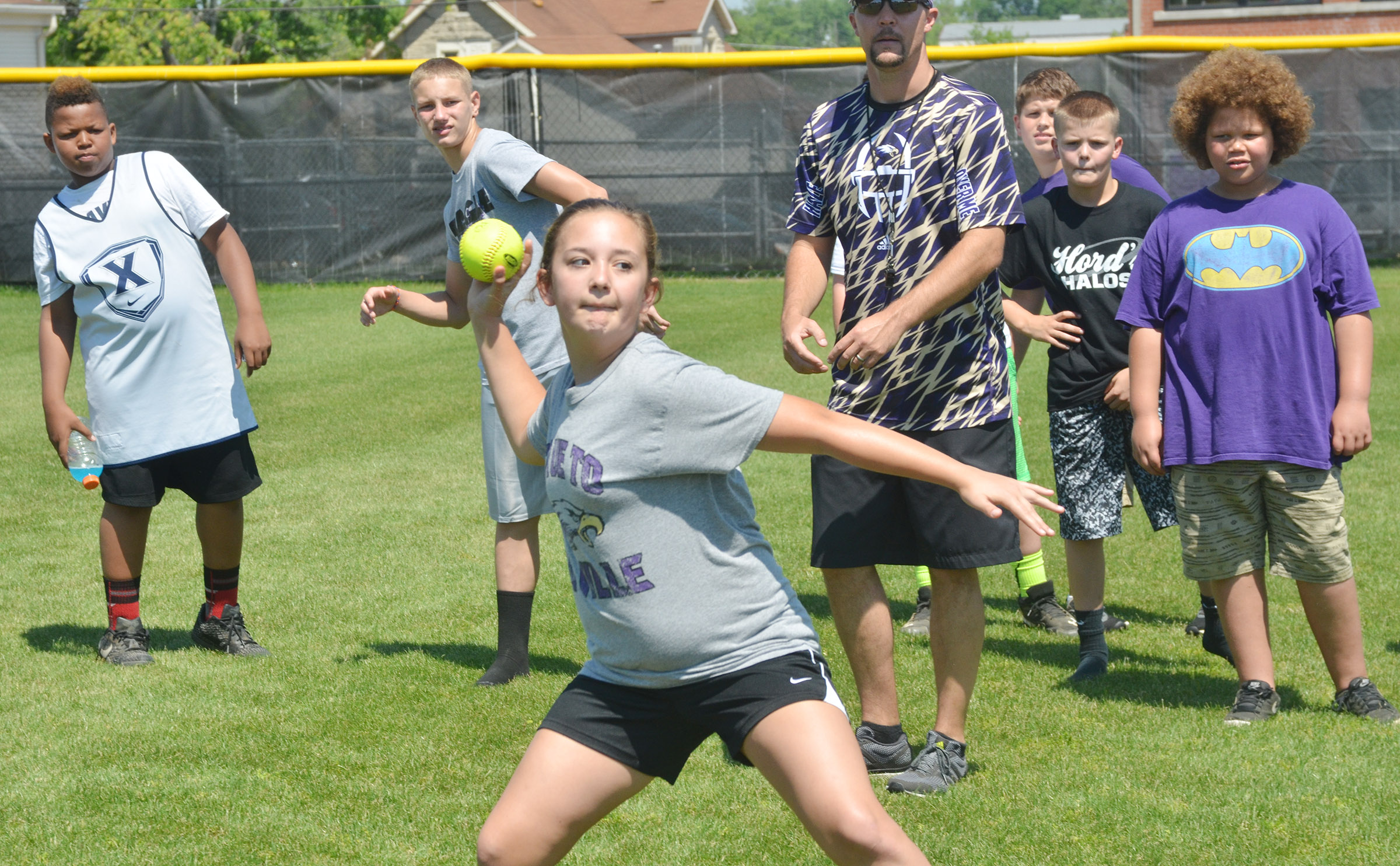 Male competitors watch as sixth-grader Briana Davis competes in the softball throw.