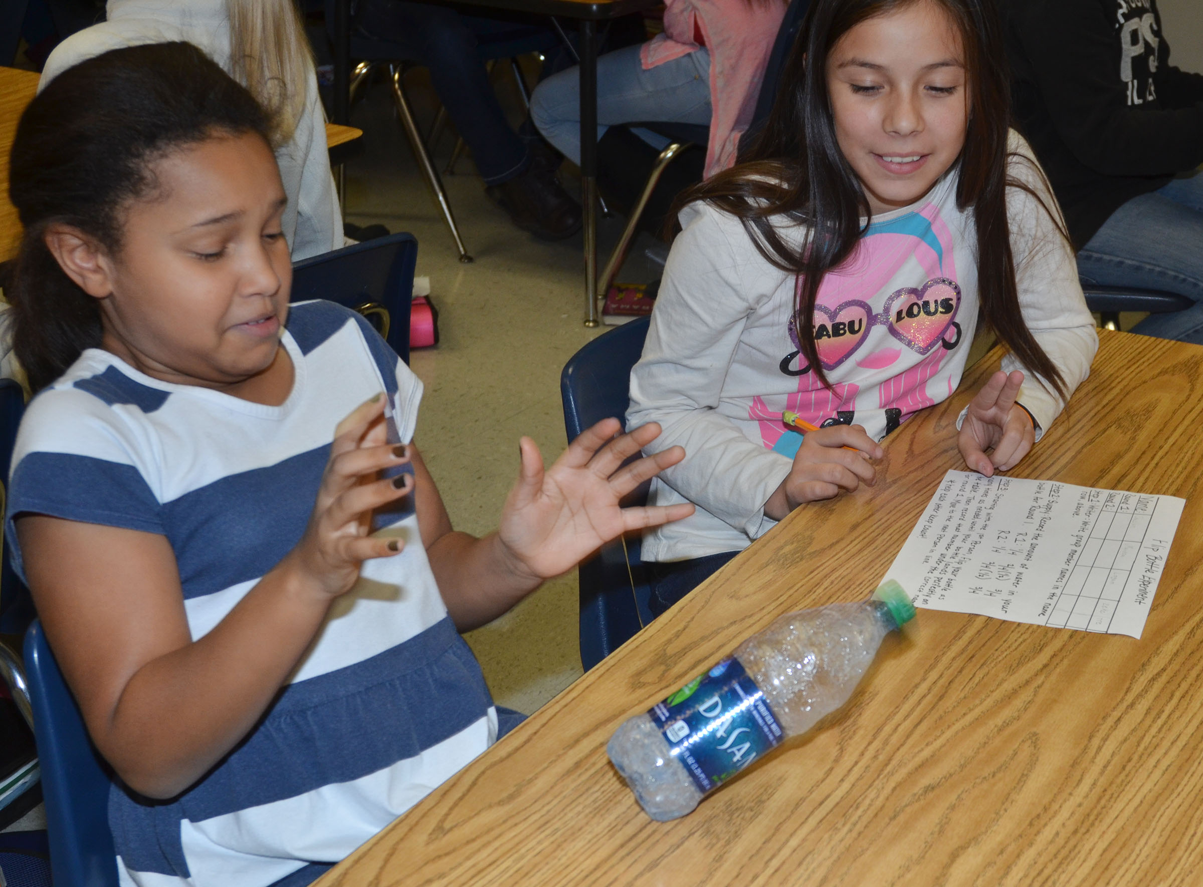 CMS fourth-graders Jaclyn Jackson, at left, reacts as her bottle drops to the table, as classmate Marissa Segura counts how many times Jackson has flipped the bottle.