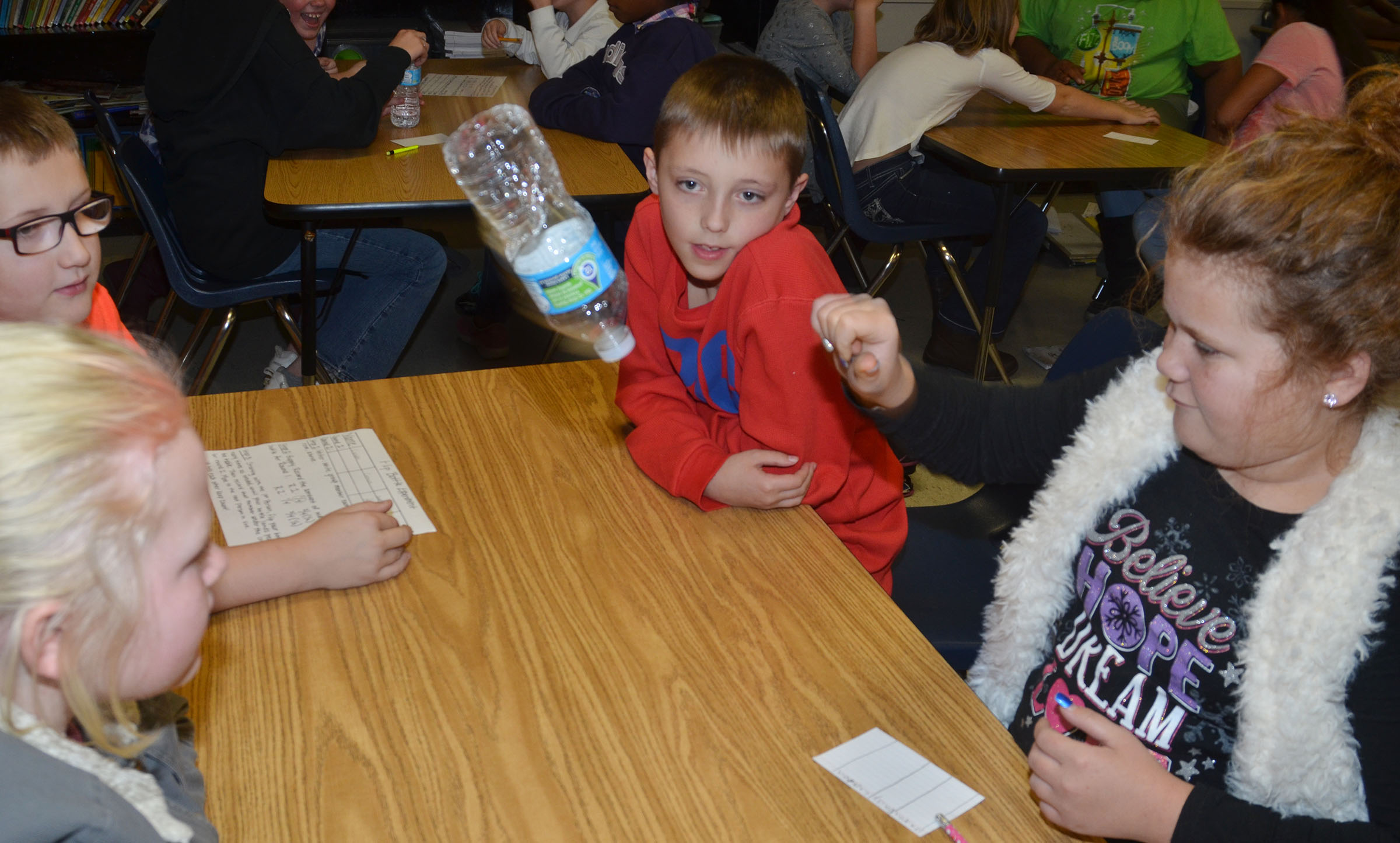 CMS fourth-grader Carmen Gurley flips her water bottle as her groupmates watch.